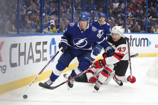 Nov 25, 2018; Tampa, FL, USA; Tampa Bay Lightning defenseman Mikhail Sergachev (98) and New Jersey Devils left wing Brett Seney (43) fight to control the puck during the second period at Amalie Arena. Mandatory Credit: Kim Klement-USA