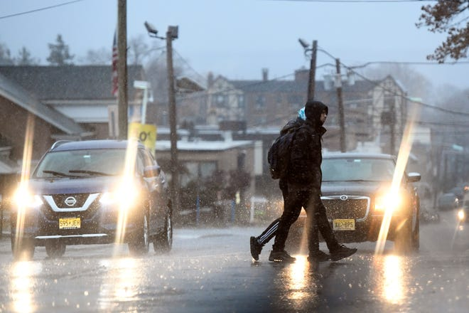 School kids cross Cedar Lane in the pouring rain on Monday, Nov. 26, 2018, in Teaneck.
