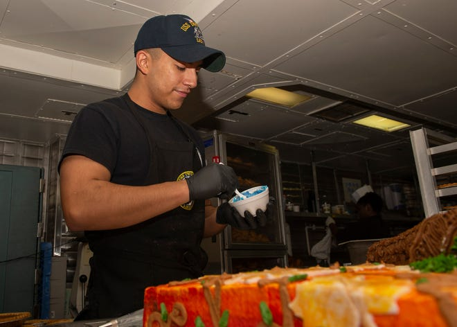US Navy Seaman Jonathan Ortiz, from Las Cruces, mixes food coloring with frosting in the bake shop aboard the Wasp-class amphibious assault ship USS Iwo Jima (LHD 7) in preparation for a Thanksgiving dinnerNov. 22. Ortiz is a culinary specialist aboard the ship. The Iwo Jima is currently underway after participating in Trident Juncture 2018, a NATO-led exercise designed to certify NATO response forces.