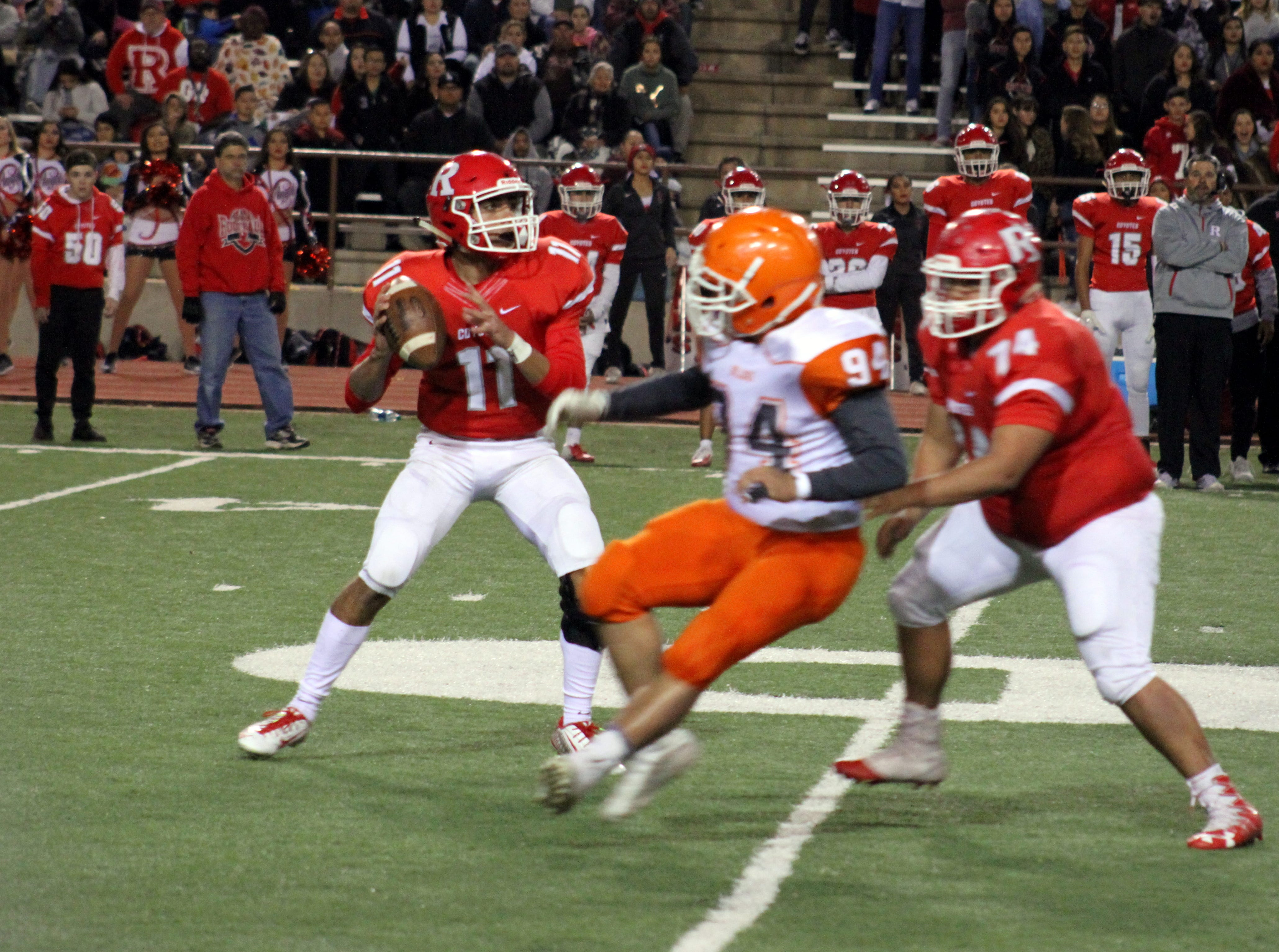 Roswell quarterback Ethan Valenzuela looks to throw while Artesia's Darian Fernandez (94) tries a spin move for a sack during Friday's Class 5A semifinal game.
