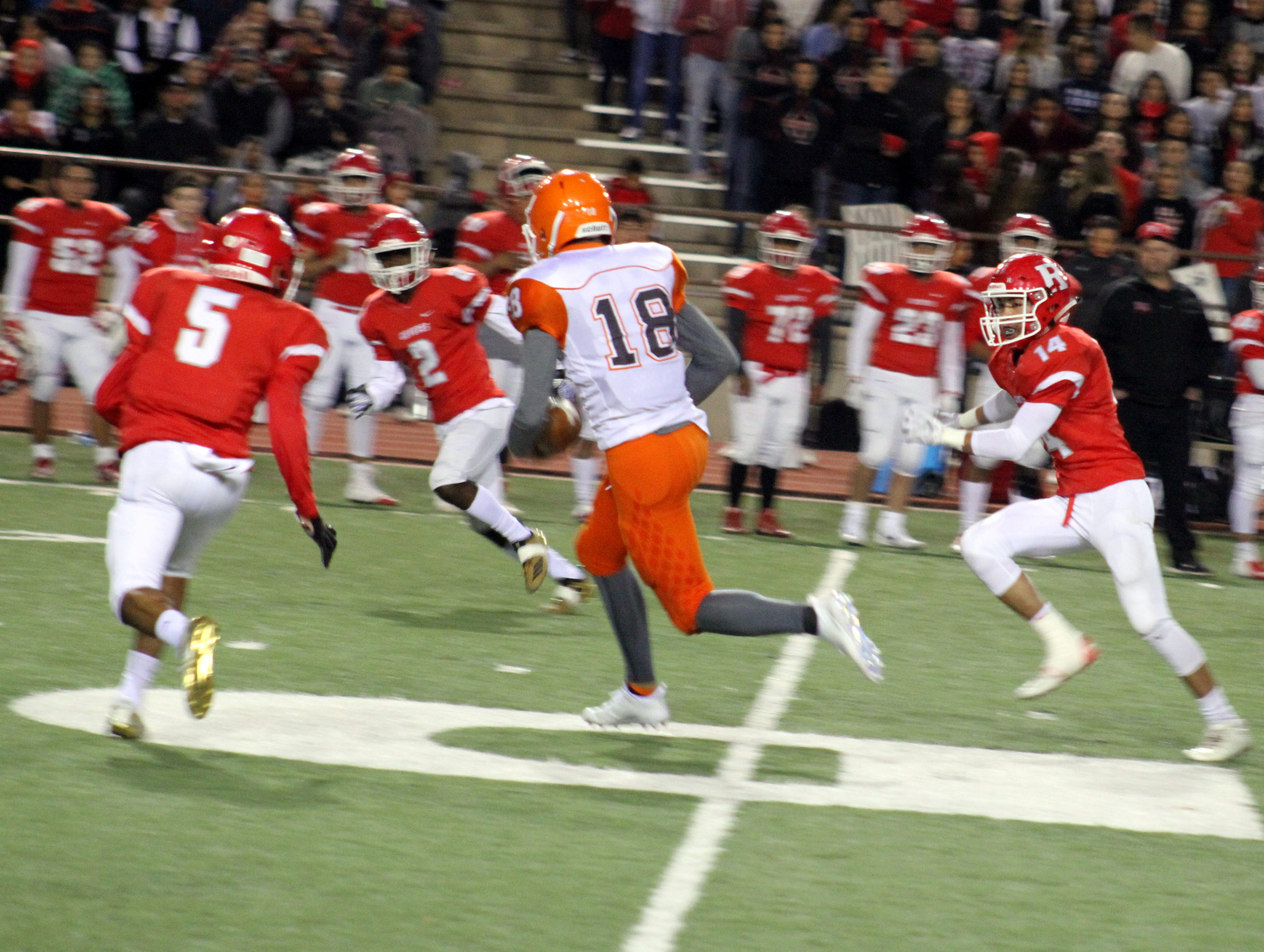 Artesia's Clay Houghtaling (18) runs between three Roswell defenders after making a catch during Friday's Class 5A semifinal game. Houghtaling finished the game with five catches for 48 yards and three rushes for 21 yards.