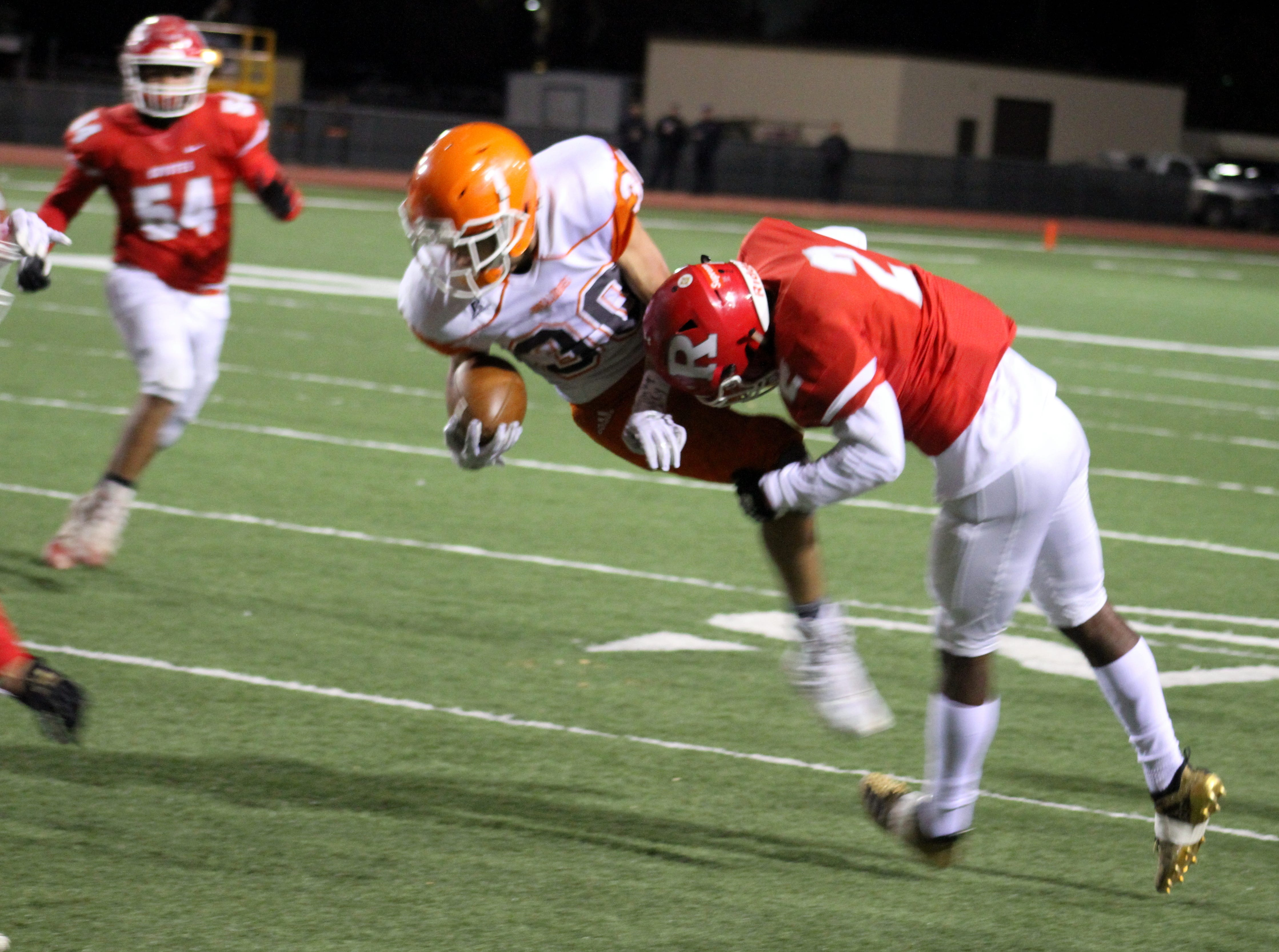 Artesia's Jagger Donaghe (30) is brought down by Roswell's Jasia Reese during Friday's Class 5A semifinal game.