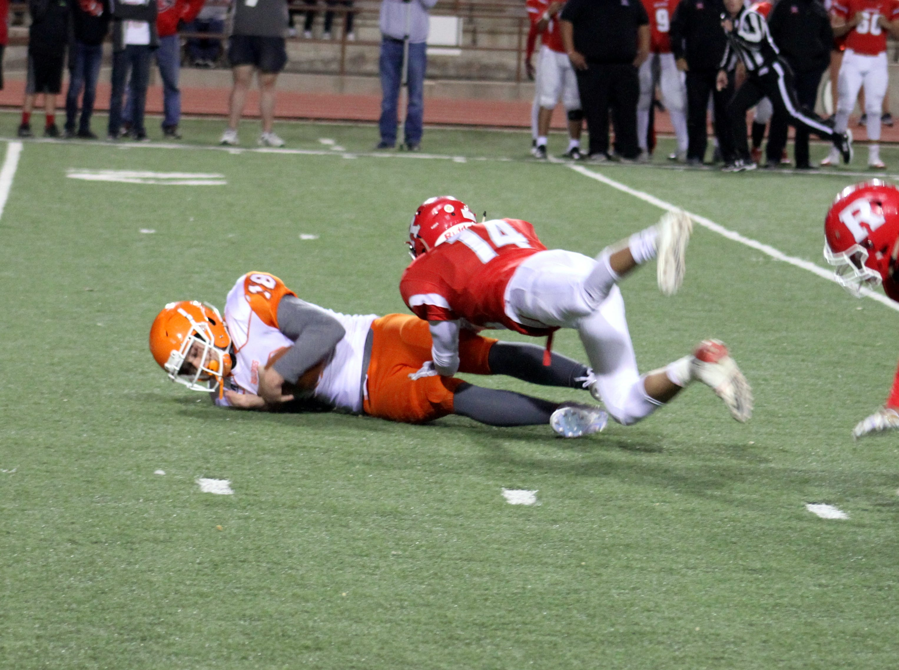Artesia's Clay Houghtaling is brought down by Roswell's Jesus Molina during Friday's Class 5A semifinal game.