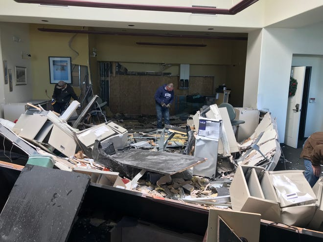 Washington Federal Bank employees clean up the mess made after a truck drove through the bank's south wall Sunday evening.