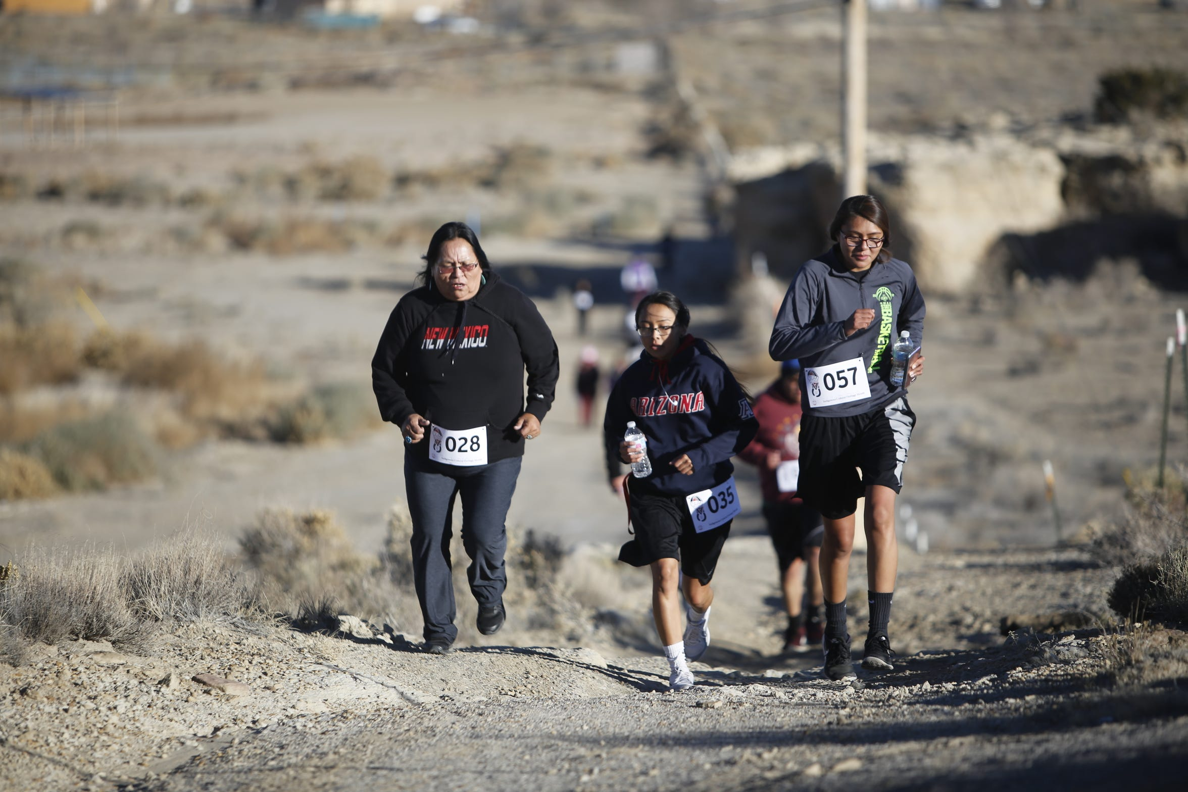 Participants run up a hill during the Clan Run on Monday at Navajo Technical University in Crownpoint.