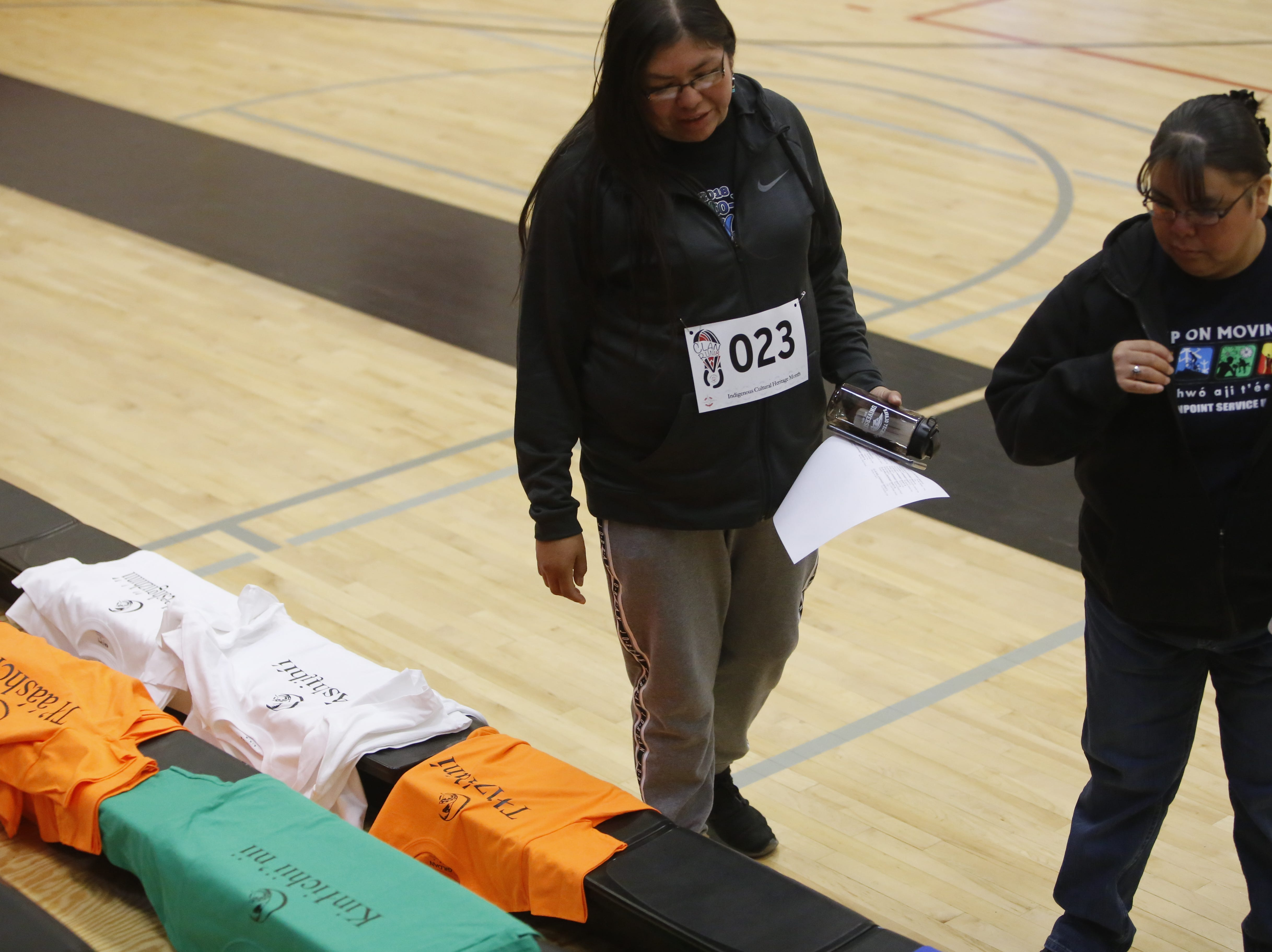 Amy Benally, left, and Devona Benally look at T-shirts that have clan names printed in the front on Monday at Navajo Technical University in Crownpoint.