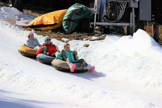 Creating a human tubing chain, these guests at Ruidoso Winter Park experience the thrill of a downhill tub ride.