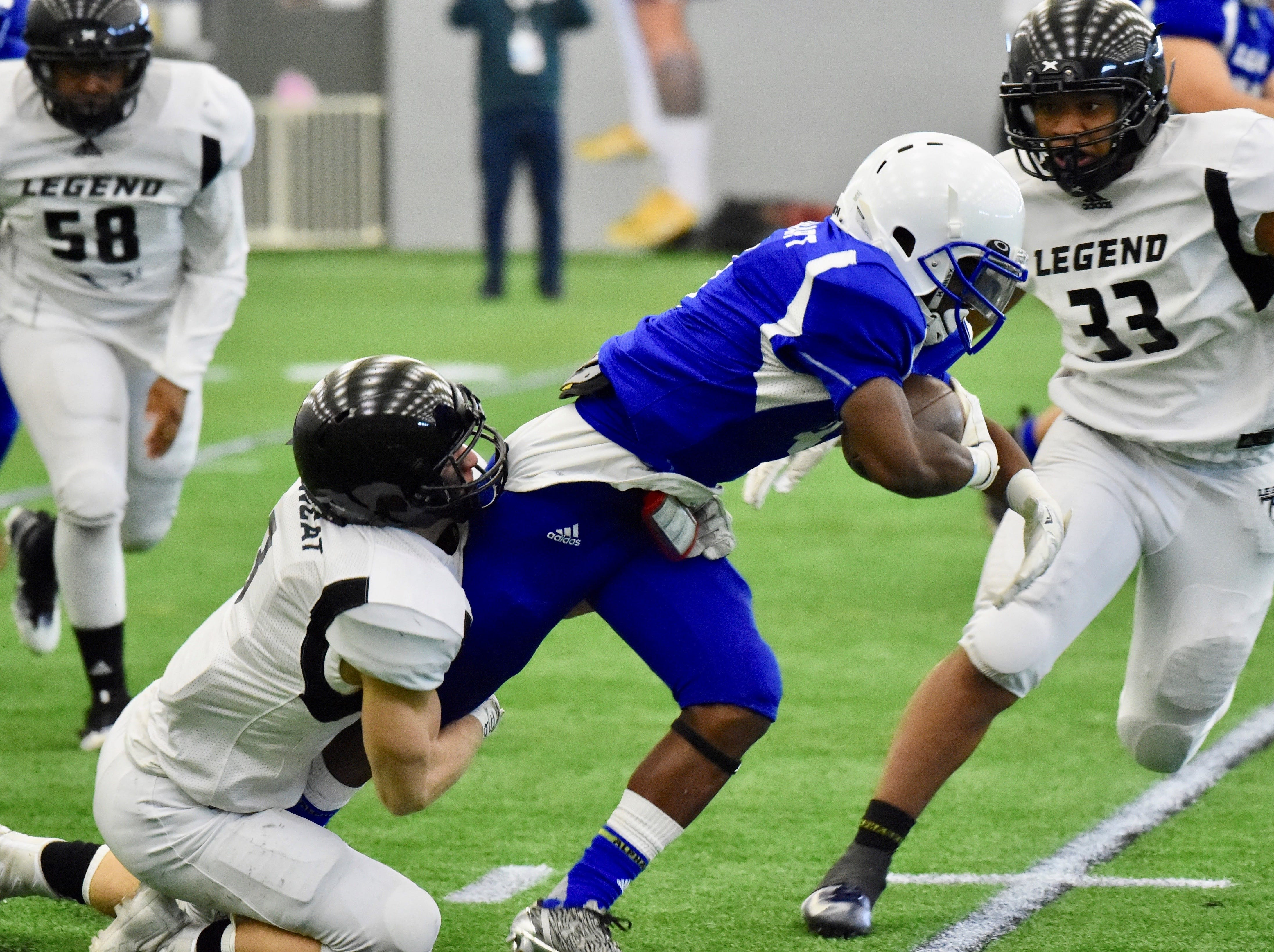 Team Legends defenders surround a Team Legacy running back. At right is Jerimiah Major (33), of Macomb Dakota.