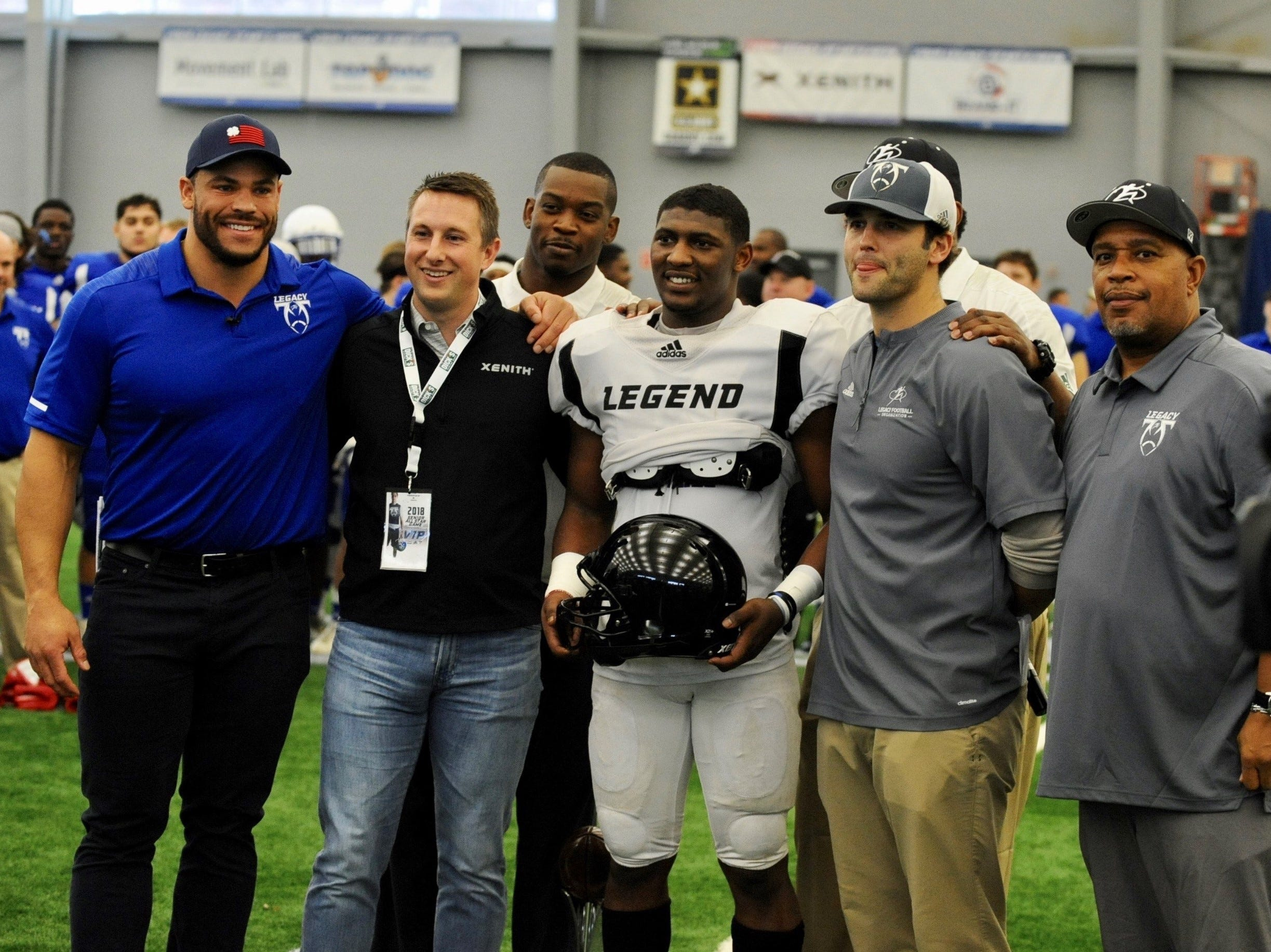 Team Legends MVP Noah Smith (Lansing Everett), poses after being presented the honor. At far left is Mike Martin, head coach of Team Legacy and formerly of the University of Michigan and NFL. Third from left is Team Legends head coach and former Michigan State and NFL player Greg Jones.