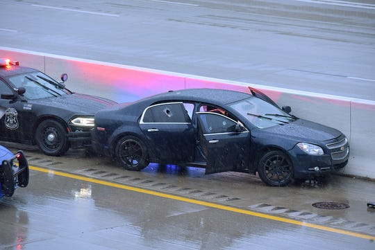 The suspect's vehicle rests against the median barrier on Westbound I-96 just west of Levan Road. A possible bullet hole is seen in the window of the rear passenger door.