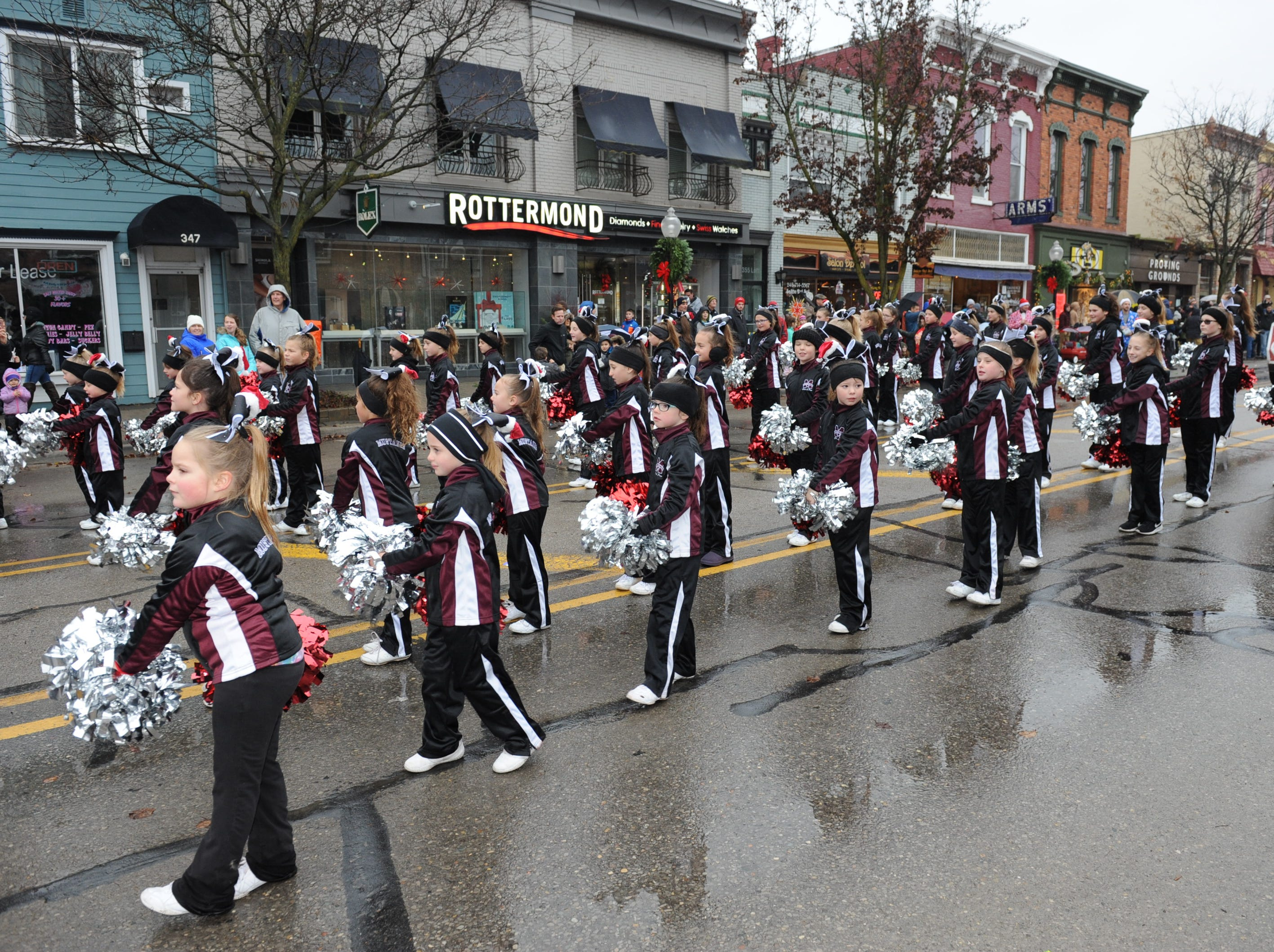The ladies from the Milford Mustangs Cheer & Pom team march in the Christmas parade in Milford Saturday morning.