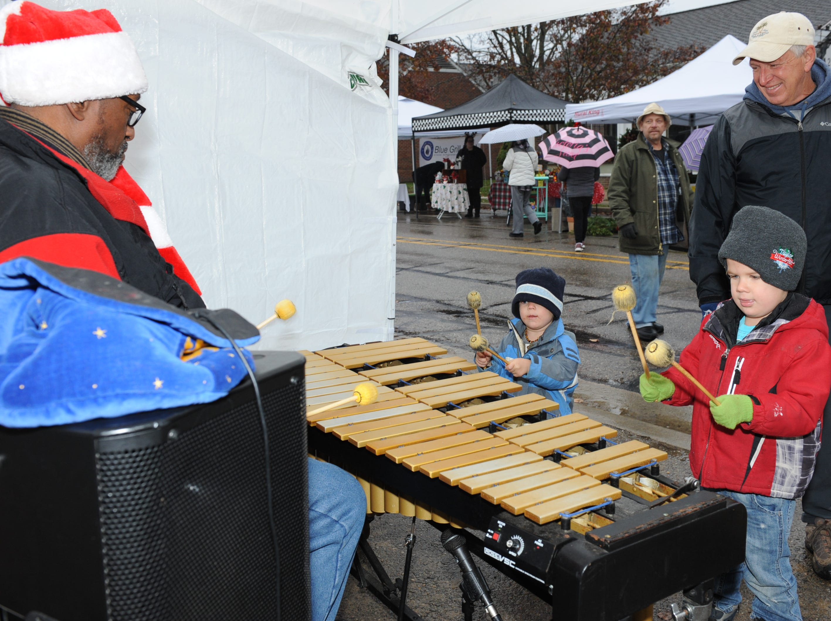 Brothers Isaac and Lucas Ratliff show off their musical skills to John Davis before the Milford Christmas Parade.