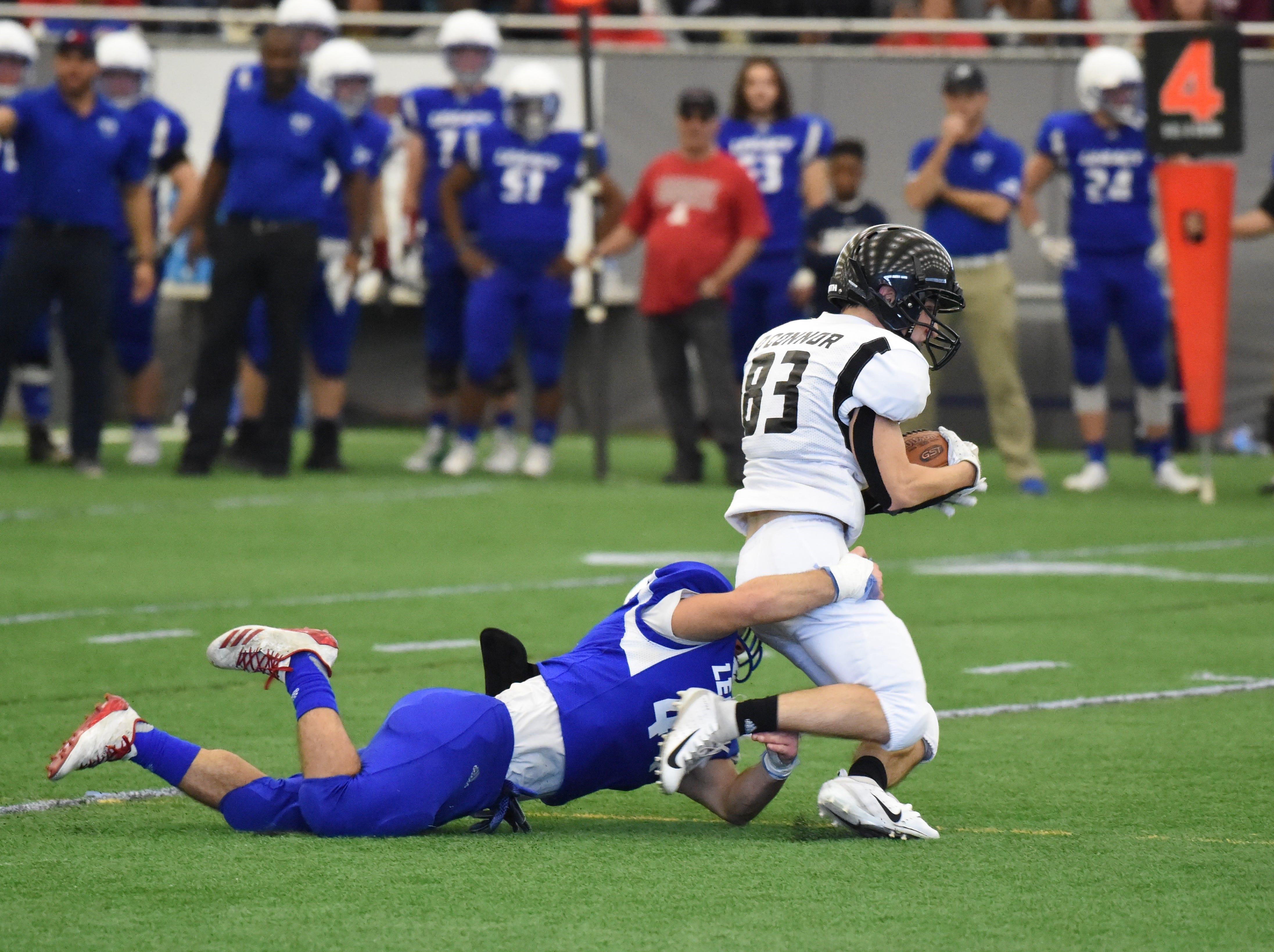 A Team Legacy defender brings down Team Legends wide receiver Drew O'Connor (83), of Novi High School.
