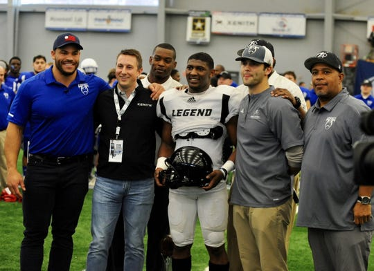 Team Legends MVP Noah Smith (Lansing Everett) poses after being presented the honor. At far left is Mike Martin, head coach of Team Legacy and formerly of the University of Michigan and NFL.