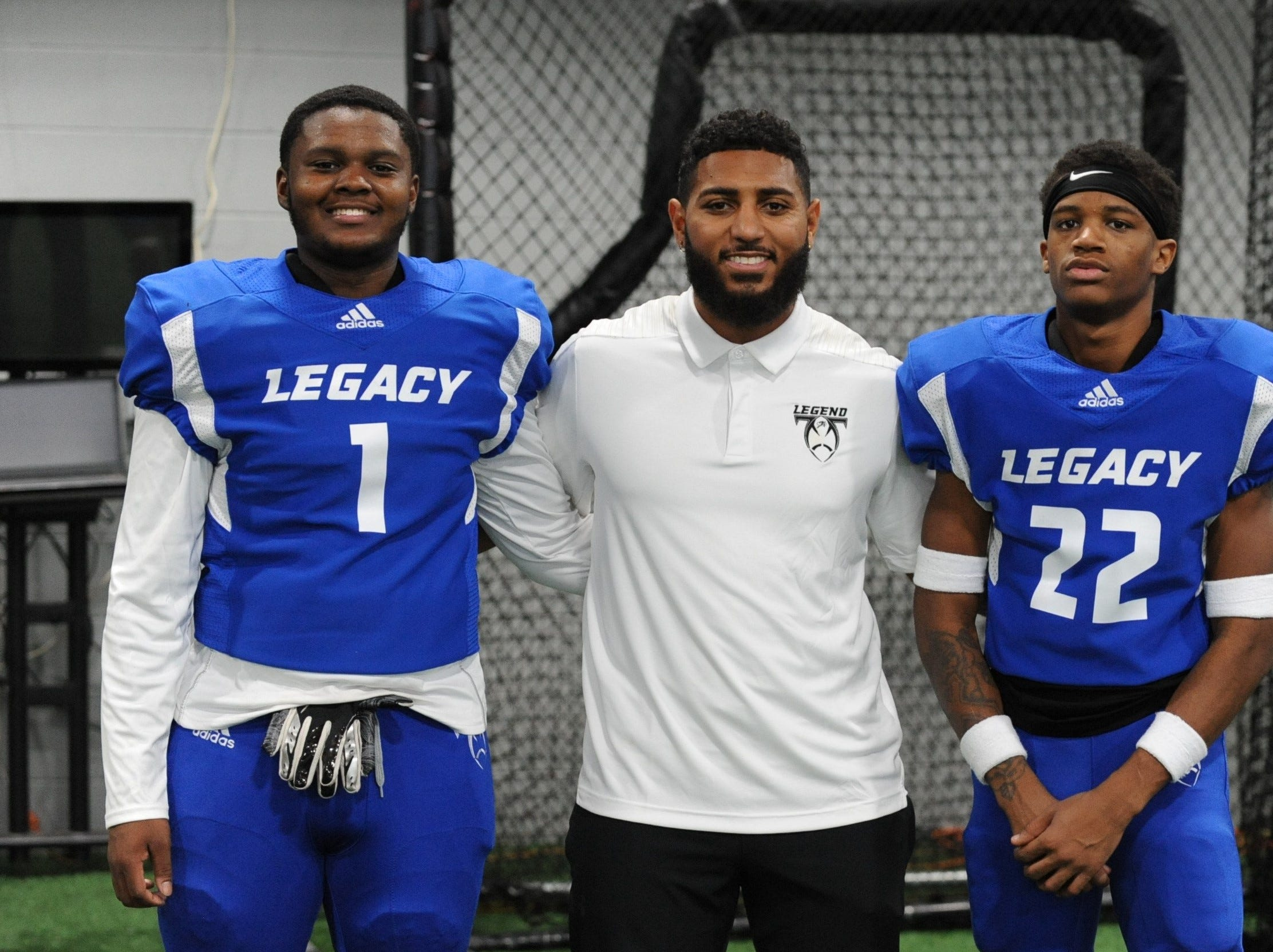Ian Iler (center), head coach at Redford Union, poses with two of his players -- Carl Ware (1) and JaJuan Stokes (22). Iler also is director of player development for Legacy Center Football in Brighton.