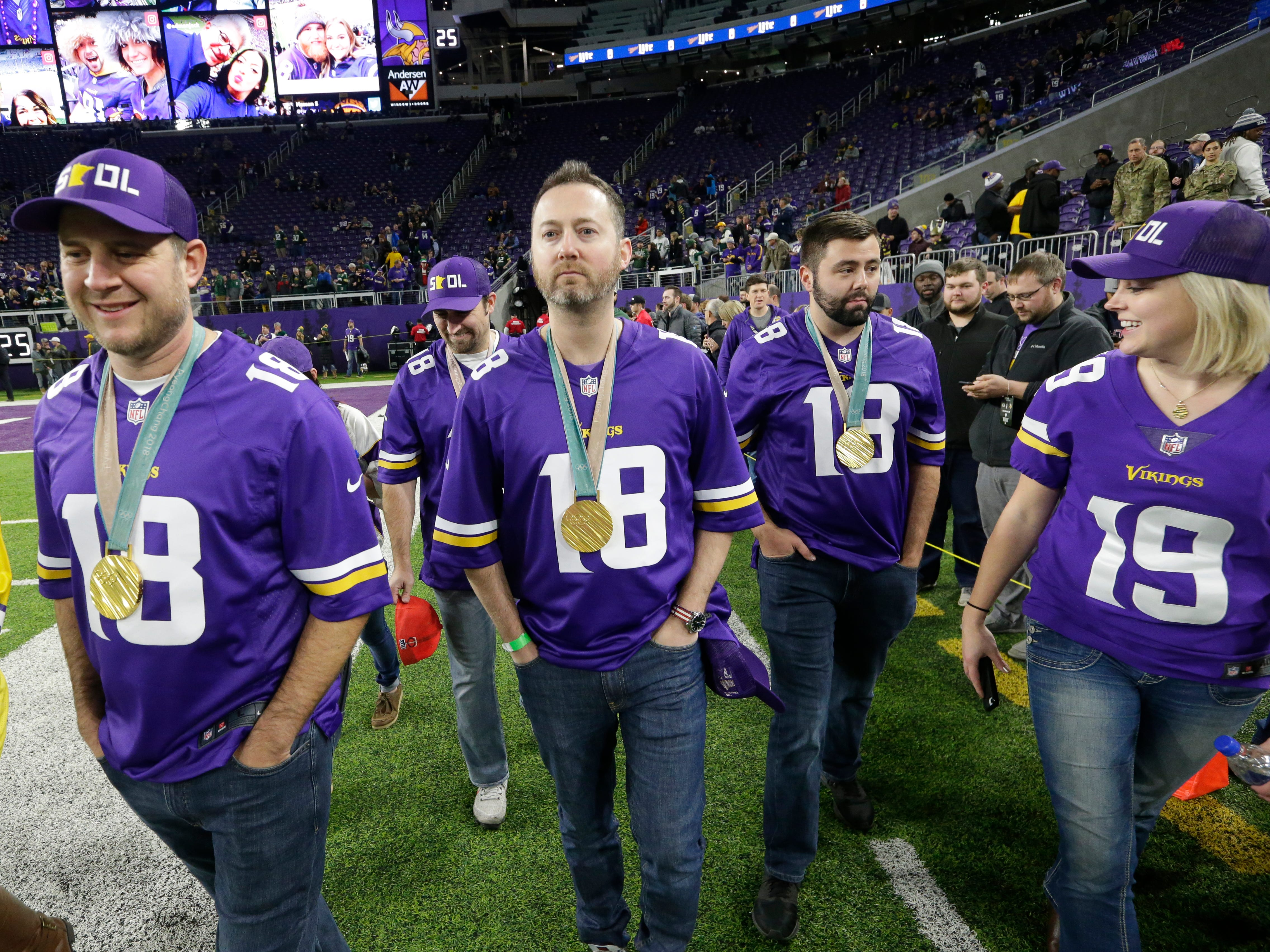 Members of the Olympic gold medal winning men's curling team members John Schuster (left), Joe Polo (rear), Tyler George and John Landsteiner are shown on the field before the Green Bay Packers game against the Minnesota Vikings Sunday, November 25, 2018 at U.S. Bank Stadium in Minneapolis, Minn.