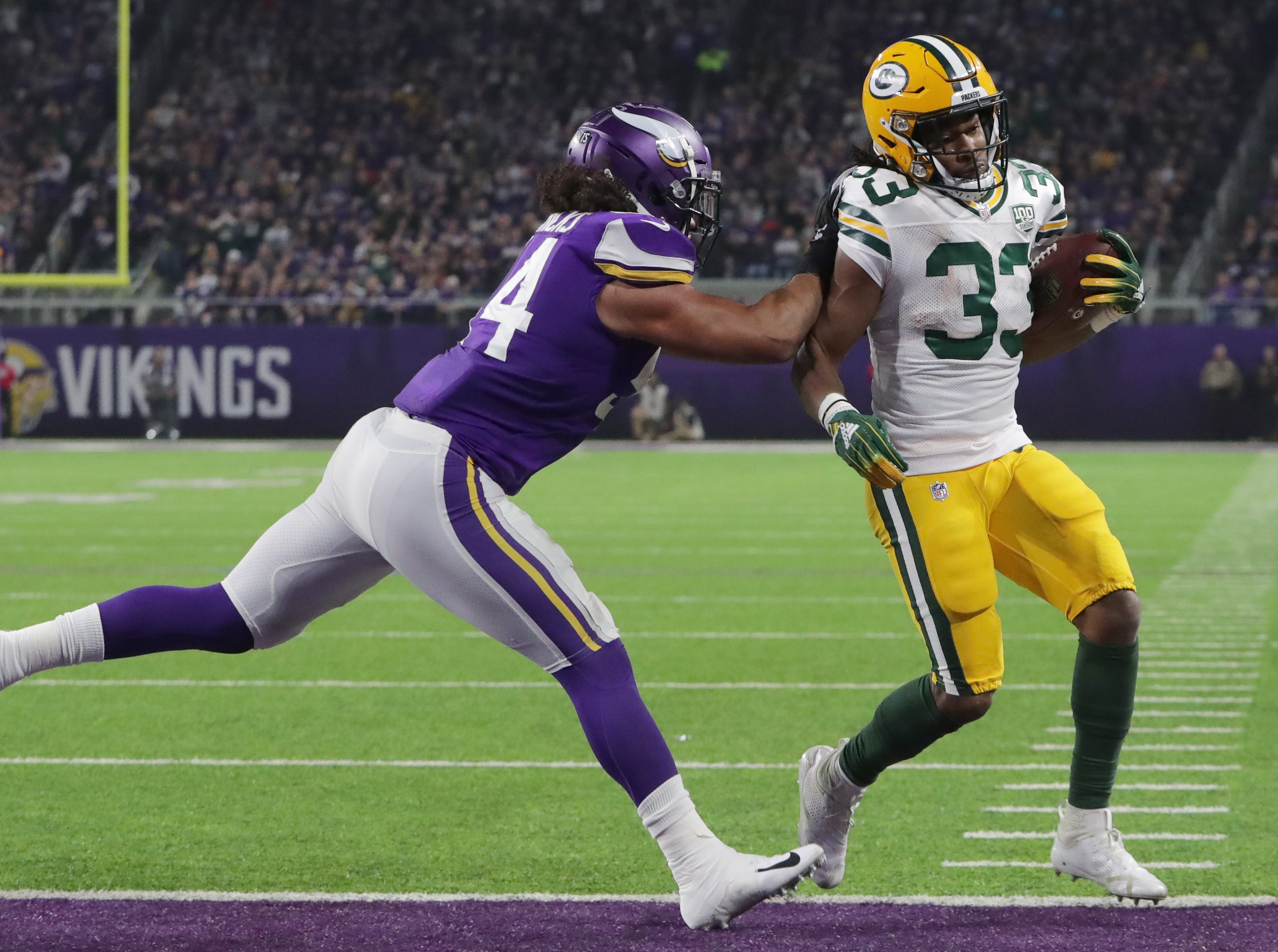 Green Bay Packers running back Aaron Jones (33) scores on a six yard run during despite the efforts of Minnesota Vikings middle linebacker Eric Kendricks (54) during the quarter of their game against the Minnesota Vikings Sunday, November 25, 2018 at U.S. Bank Stadium in Minneapolis, Minn.