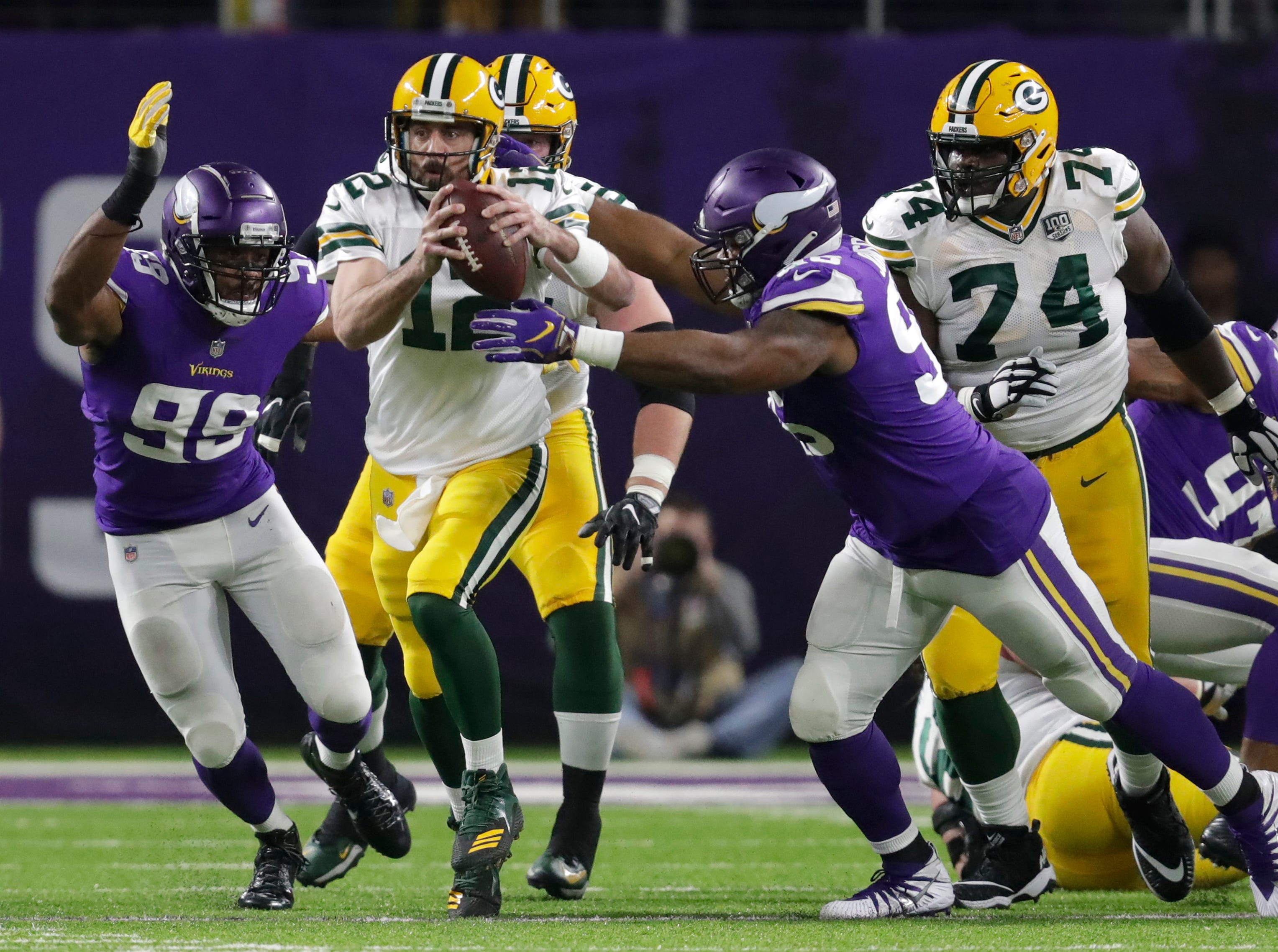 Green Bay Packers quarterback Aaron Rodgers (12) is brought down by Minnesota Vikings defensive end Danielle Hunter (99) and defensive tackle Tom Johnson (96) in the second quarter during their football game Sunday, November 25, 2018, at U.S. Bank Stadium in Minneapolis, Minn. 