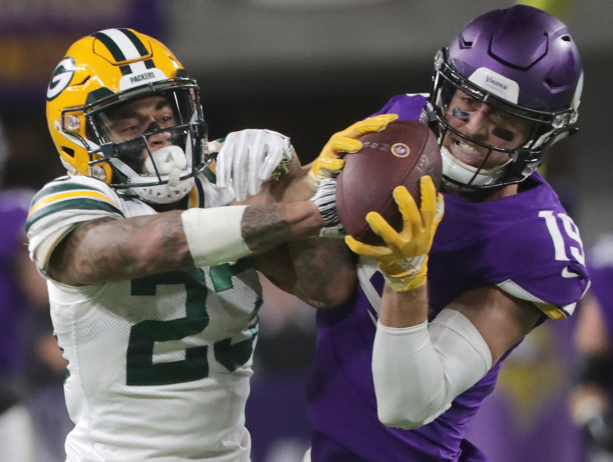 Minnesota Vikings wide receiver Adam Thielen (19) wrestles the ball from Green Bay Packers cornerback Jaire Alexander (23) for a 20-yarrd reception during the second quarter of their game against the Minnesota Vikings Sunday, November 25, 2018 at U.S. Bank Stadium in Minneapolis, Minn.