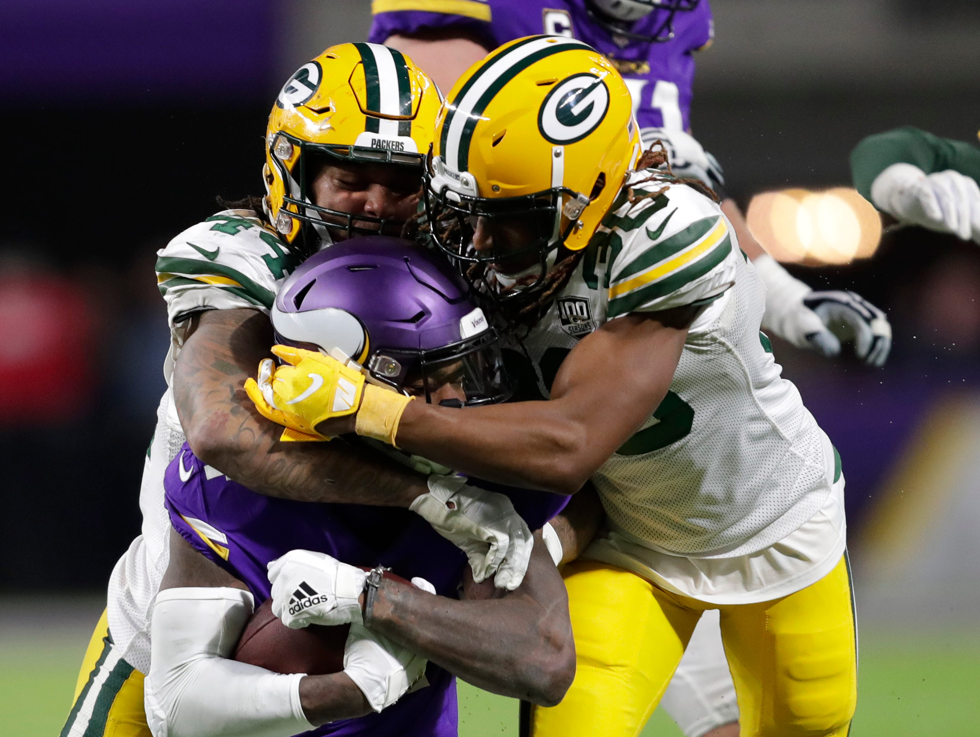 Green Bay Packers inside linebacker Antonio Morrison (44) and cornerback cornerback Tramon Williams (38) tackle Minnesota Vikings wide receiver Stefon Diggs (14) in the second half during their football game Sunday, November 25, 2018, at U.S. Bank Stadium in Minneapolis, Minn. 