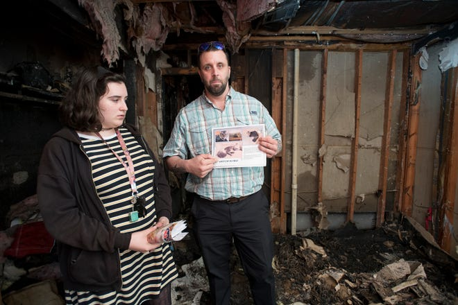 Ryan Ward and his daughter Chloe, 16, hold a flyer for their missing cat  as they stand in their fire destroyed apartment in Gulf Breeze on Monday, November 26, 2018.  The cat has been missing since the fire and they believe that it may have escaped the flames.