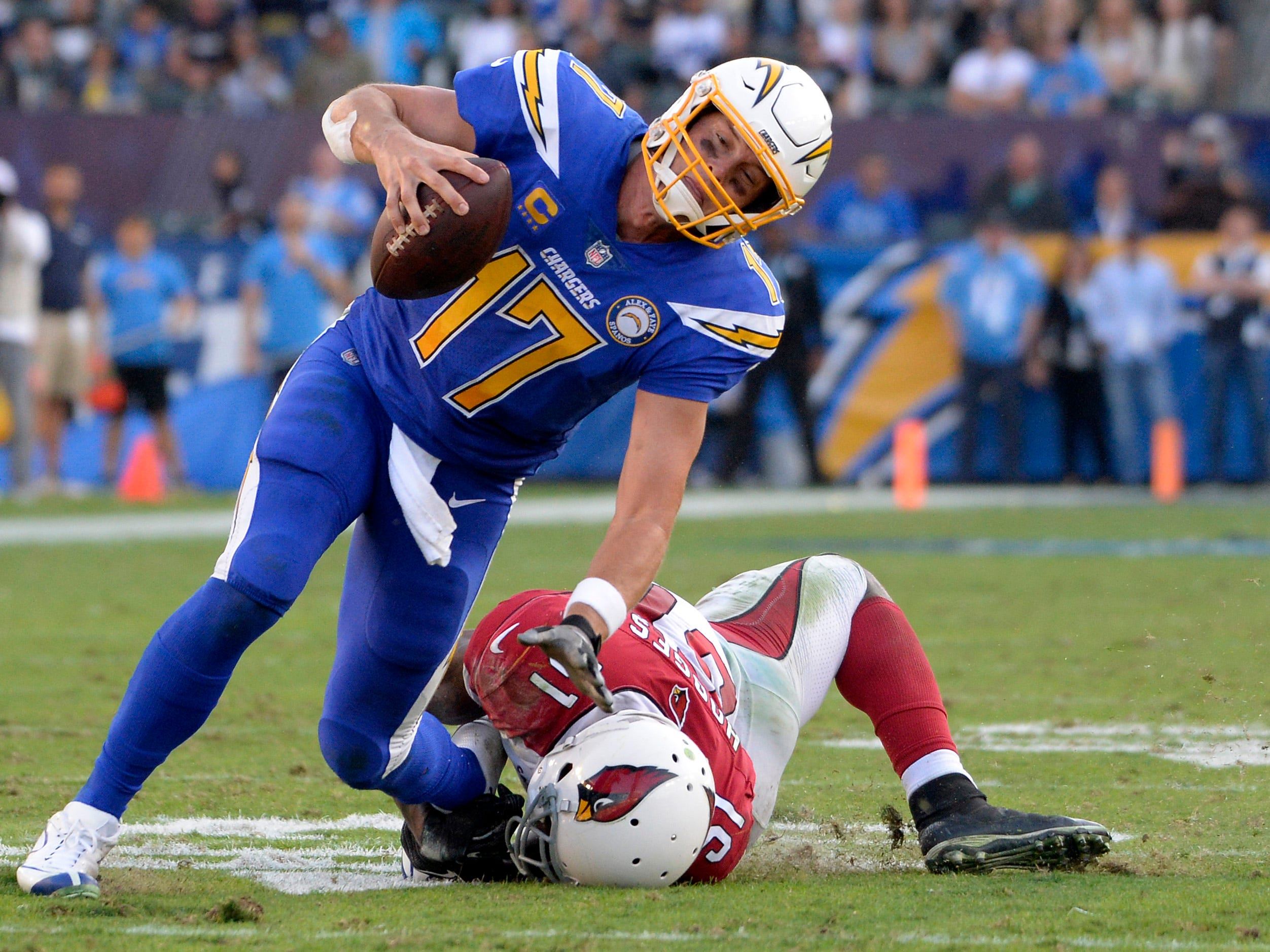 Nov 25, 2018; Carson, CA, USA; Los Angeles Chargers quarterback Philip Rivers (17) is tackled by Arizona Cardinals linebacker Gerald Hodges (51) during the third quarter at StubHub Center.