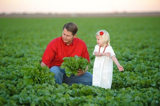 Yuma farmer John Boelts picks lettuce in 2011 with his daughter, Daisy.