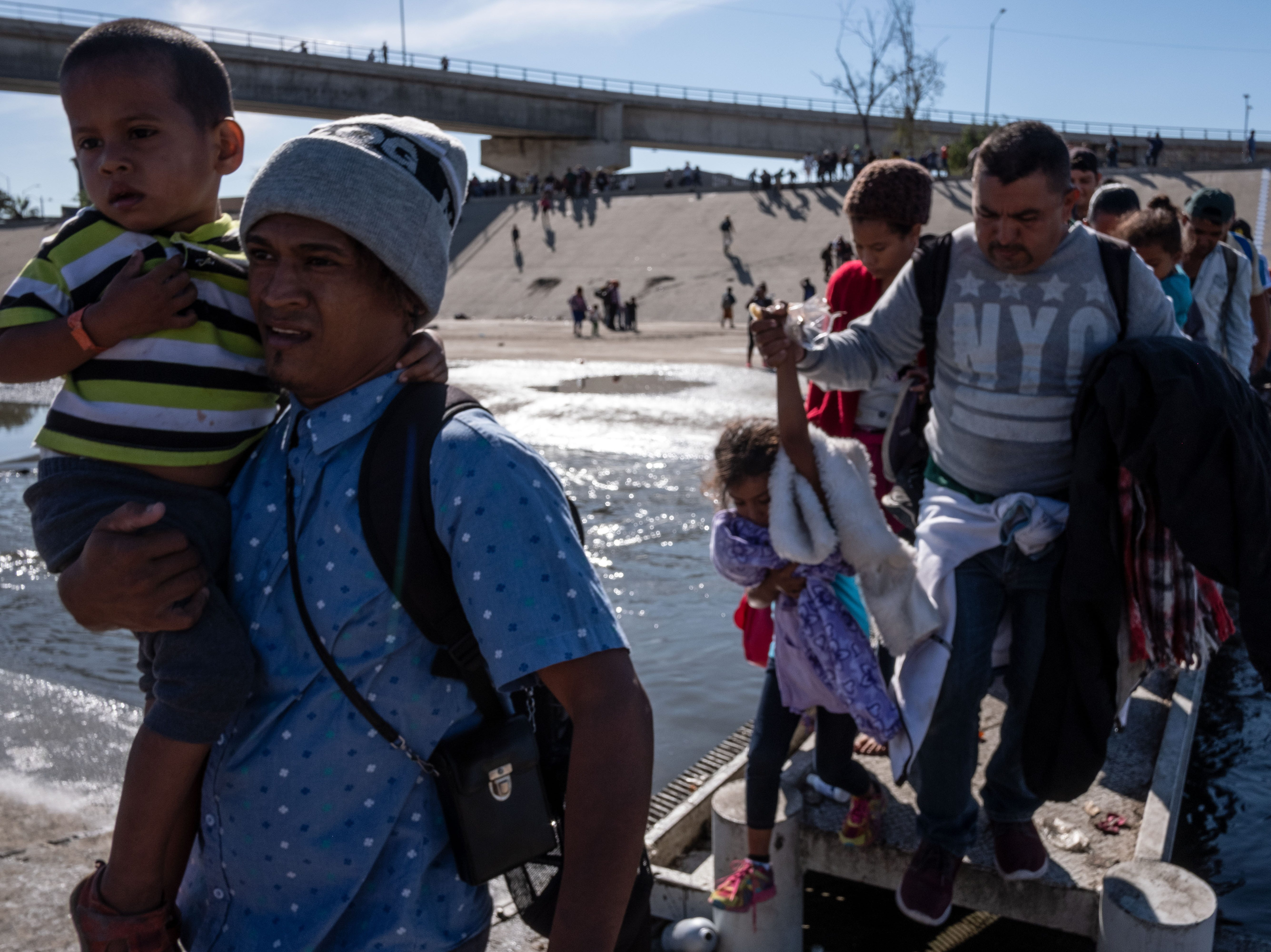Un grupo de migrantes centroamericanos, principalmente de Honduras, cruzan el río Tijuana en un intento por llegar al cruce fronterizo de El Chaparral en la frontera México-Estados Unidos, en Tijuana, estado de Baja California, México, el 25 de noviembre. 2018