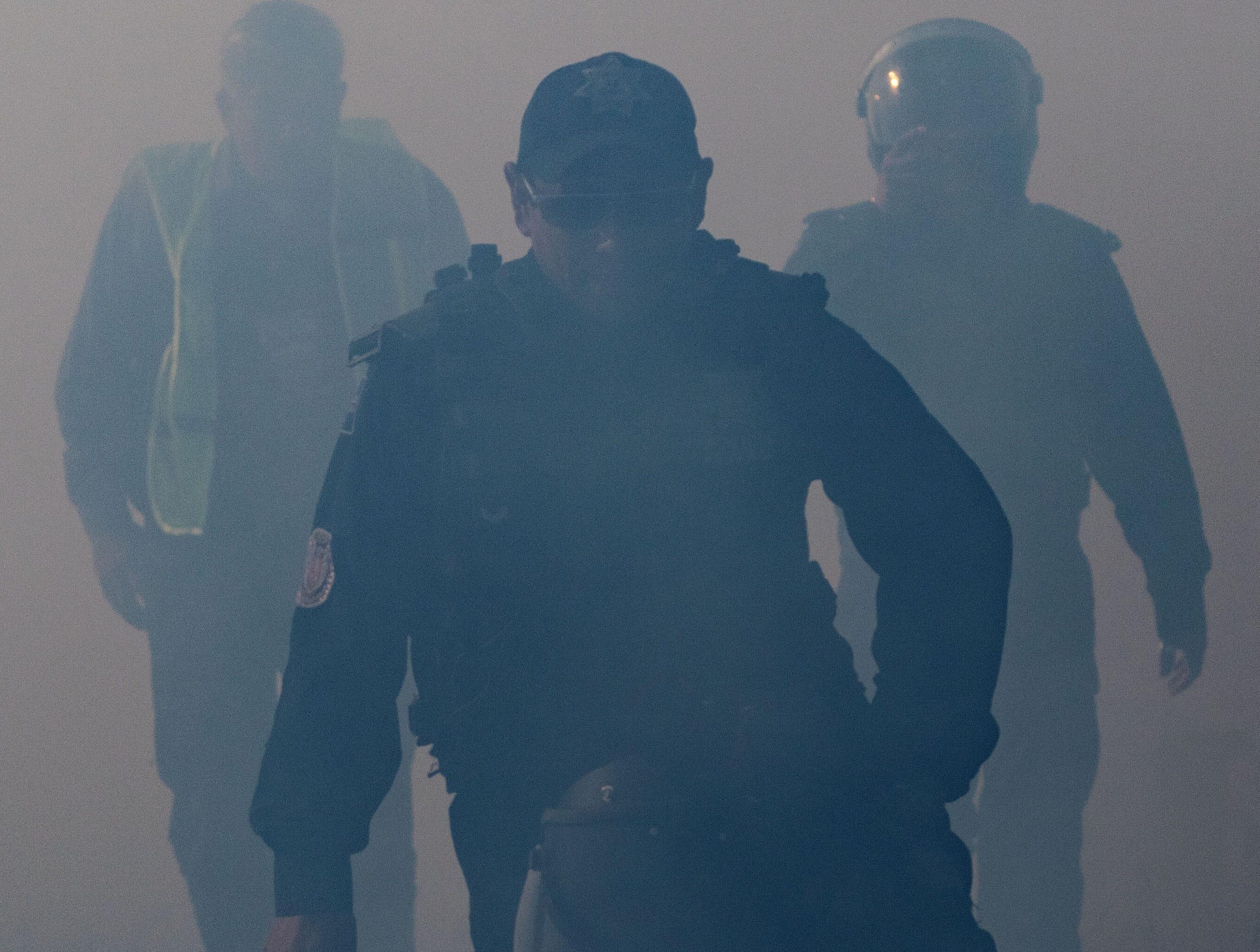 Los oficiales de la Policía Federal de México son vistos a través del humo de gas lacrimógeno lanzado por la Patrulla Fronteriza de los Estados Unidos para dispersar a los migrantes centroamericanos, principalmente hondureños, después de una supuesta disputa verbal, cerca del cruce de la frontera de El Chaparral en Tijuana, estado de Baja California, México, cerca de la frontera el 25 de noviembre de 2018.