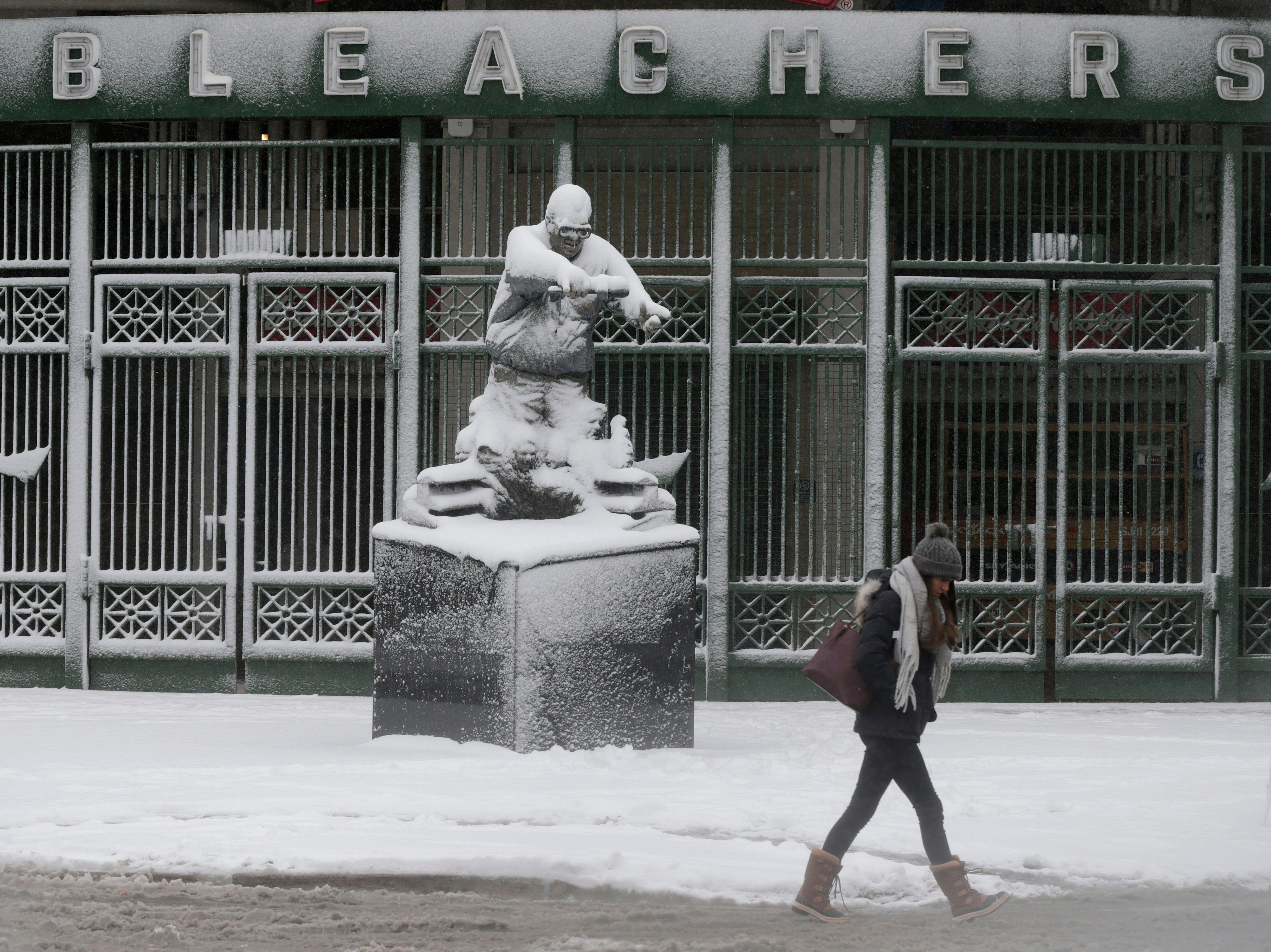 Transeúntes caminan junto a la estatua del famoso locutor de los Chicago Cubs, Harry Carey, frente al Wrigley Field, el lunes 26 de noviembre de 2018, en Chicago. Una tempestad invernal trajo condiciones de tormenta de nieve a partes del Medio Oeste el lunes temprano, aterrizando cientos de vuelos y causando un caos en el tráfico mientras los viajeros regresaban al trabajo después del fin de semana de Acción de Gracias.