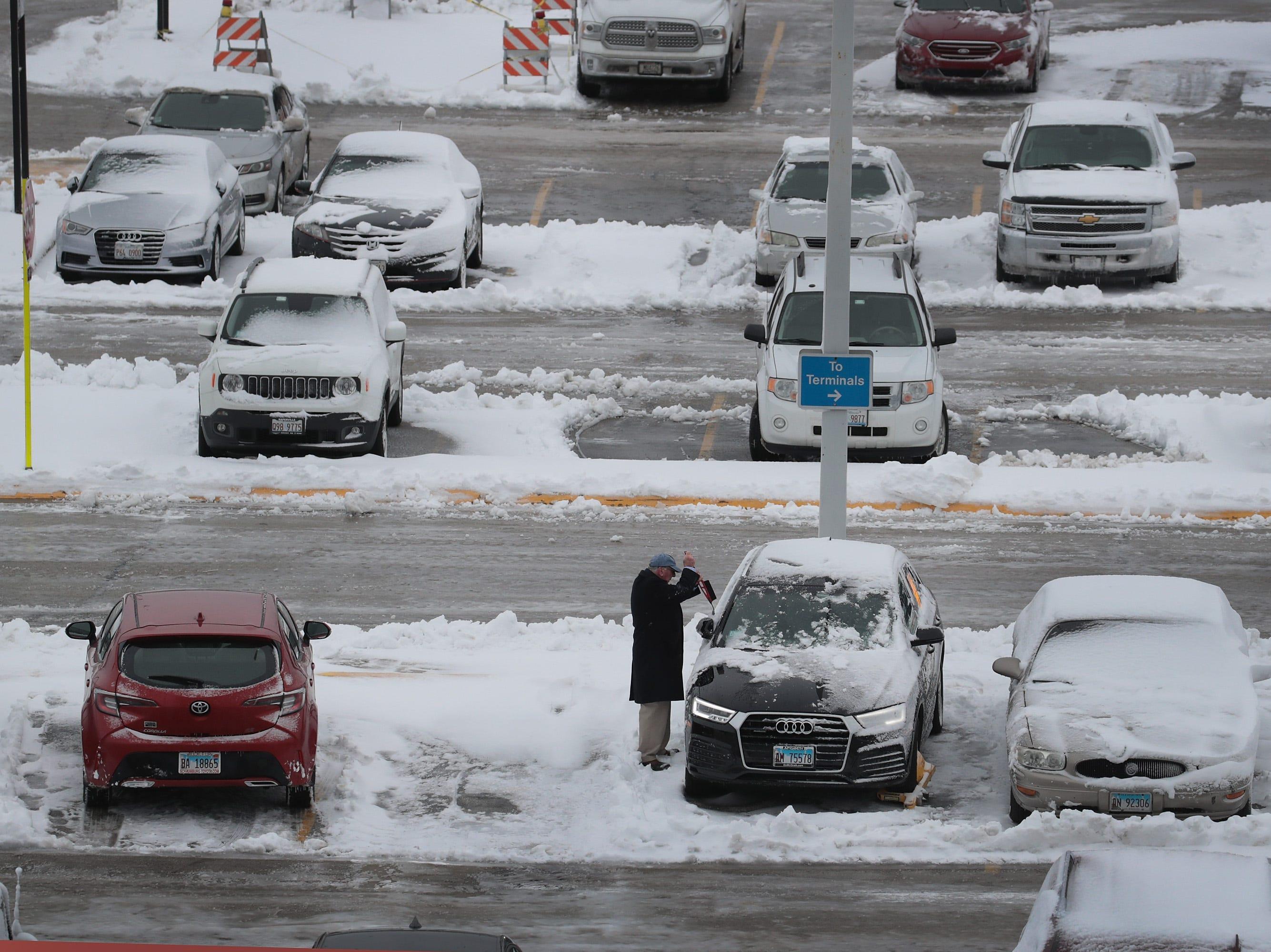Un automovilista quita la nieve de su automóvil en el Aeropuerto Internacional O'Hare luego de la tormenta de nieve del 26 de noviembre de 2018 en Chicago, Illinois. La tormenta, que se elevó hasta un pie de nieve en Chicago y sus alrededores, causó el retraso y la cancelación de cientos de vuelos, causó decenas de accidentes de tráfico y dejó a miles sin electricidad.