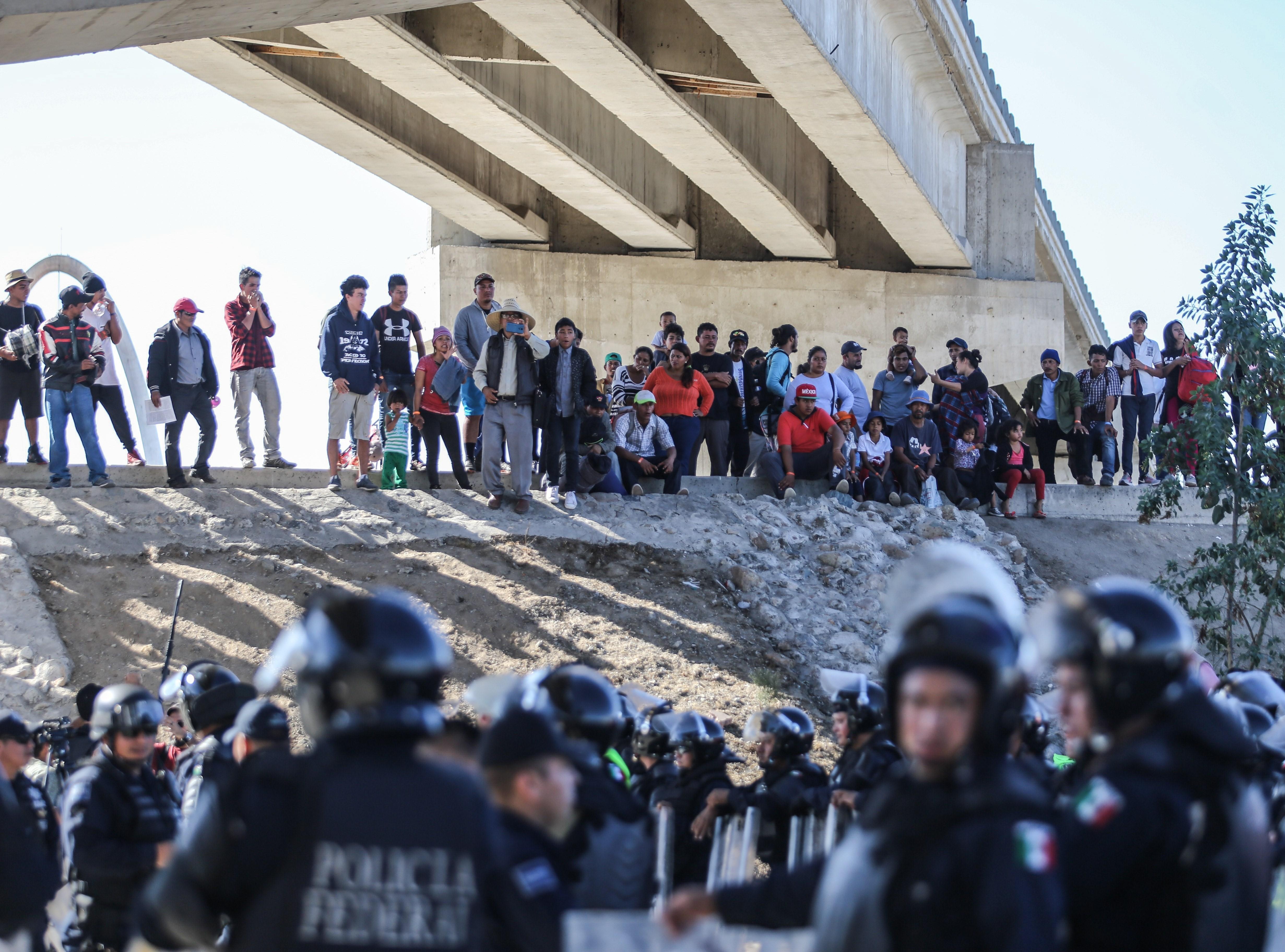 Un grupo de migrantes de la caravana de centroamericanos que avanzó el domingo 25 de noviembre de 2018, hacia la garita de San Ysidro, EE.UU. se desvió de la ruta prevista para intentar cruzar el muro fronterizo por otros puntos, en tanto la policía fronteriza estadounidense les lanzó gas lacrimógeno.