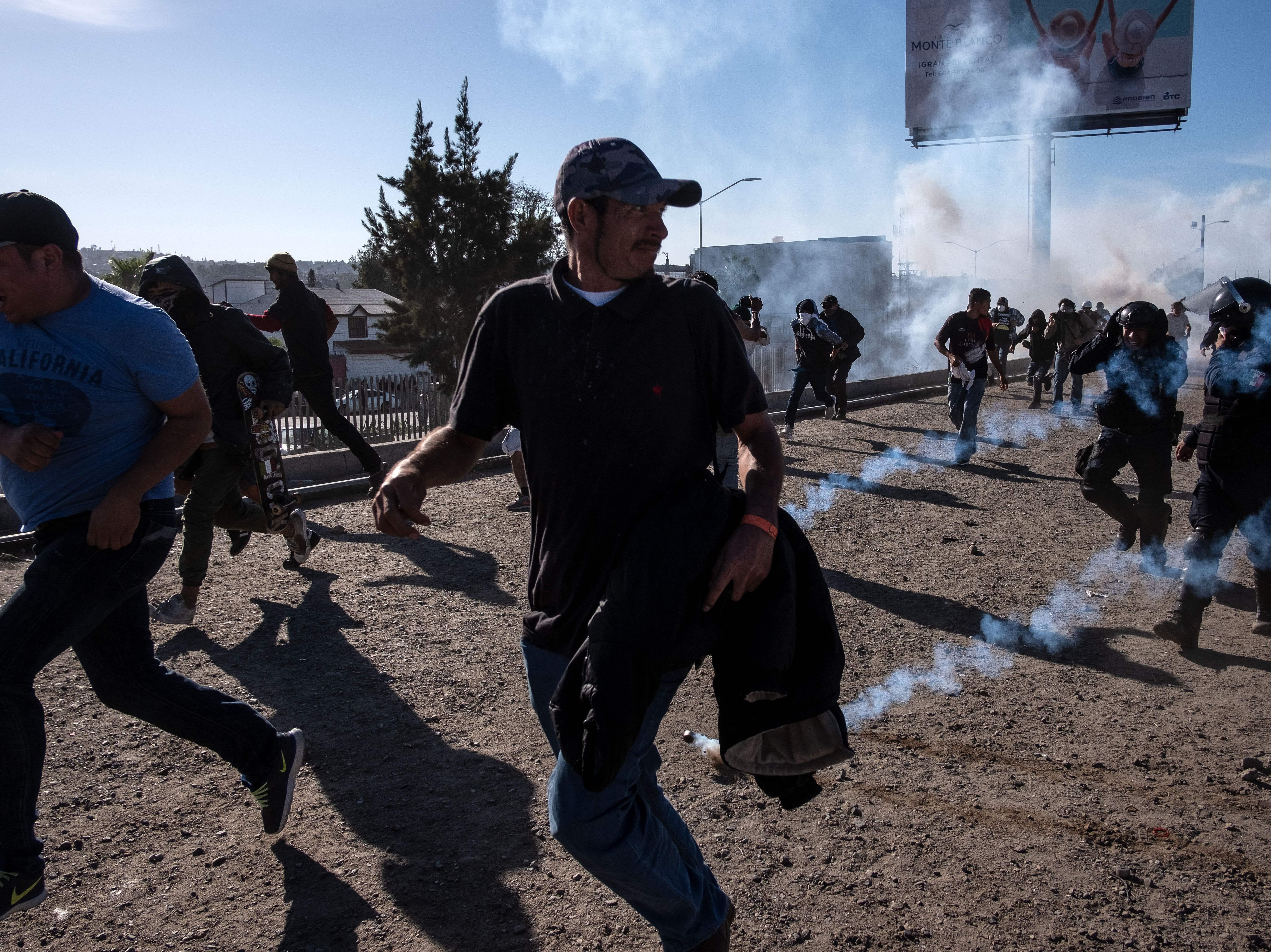 Los migrantes centroamericanos, en su mayoría hondureños, corren a lo largo del río Tijuana cerca del cruce fronterizo de El Chaparral en Tijuana, estado de Baja California, México, cerca de la frontera entre EE. UU. y México, después de que la patrulla fronteriza de EE. UU. arrojara gas lacrimógeno desde la distancia para dispersarlos después de un supuesta disputa verbal, el 25 de noviembre de 2018.