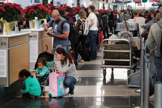 Los pasajeros intentan tomar vuelos desde el Aeropuerto Internacional O'Hare después de que una tormenta de nieve causó la demora y cancelación de cientos de vuelos en el aeropuerto el 26 de noviembre de 2018 en Chicago, Illinois. La tormenta, que se elevó a un pie de nieve en Chicago y sus alrededores, también causó decenas de accidentes de tráfico y dejó a miles de personas sin electricidad.