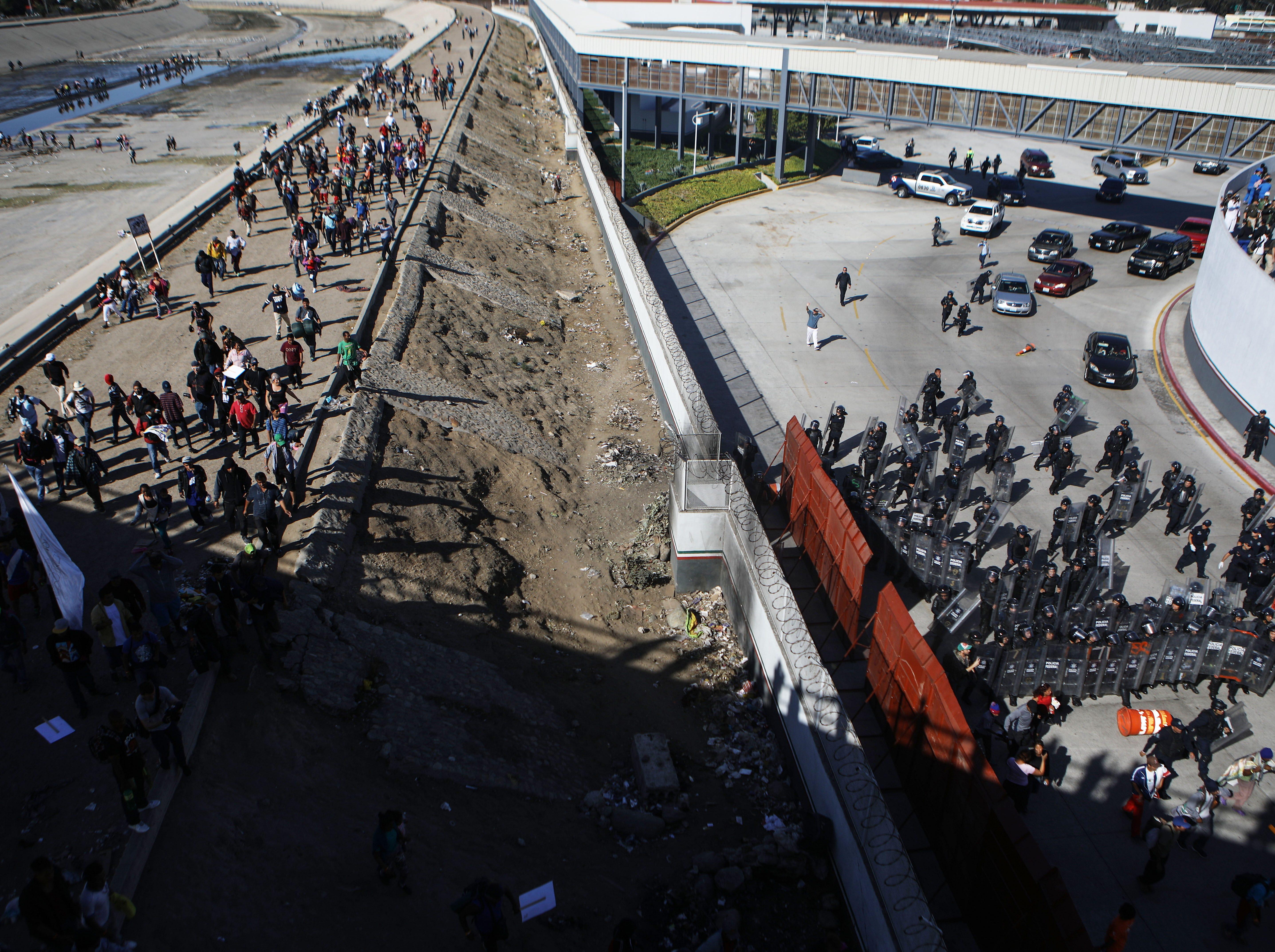 La policía mexicana hace guardia (der) mientras los inmigrantes caminan en una orilla del río Tijuana, casi seco, mientras se dirigen hacia el puerto de entrada de El Chaparral, después de sortear un bloqueo policial, el 25 de noviembre de 2018 en Tijuana, México.