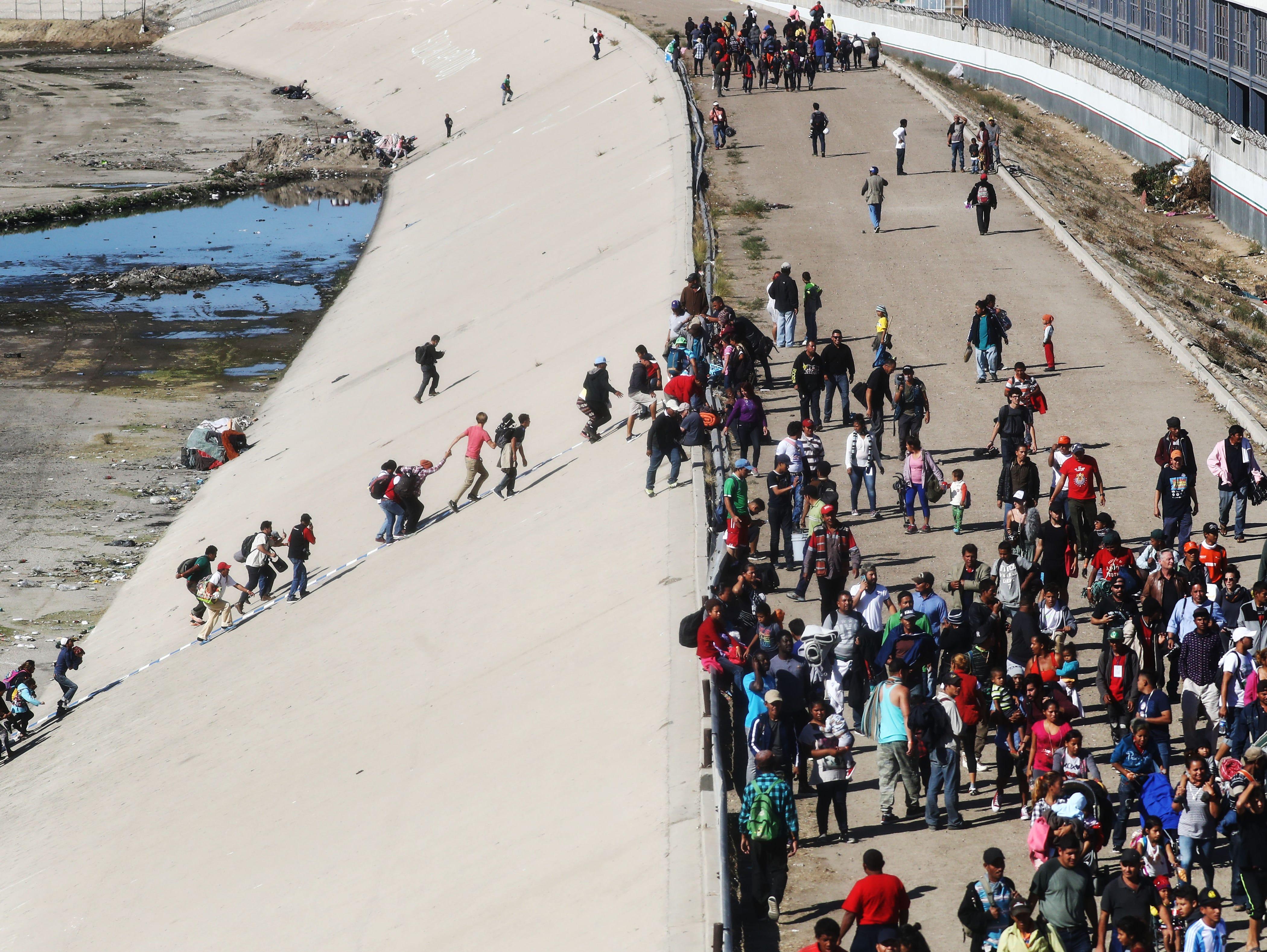 Los migrantes suben a la orilla del río Tijuana, casi seco, mientras intentan pasar el bloqueo policial al puerto de entrada de El Chaparral el 25 de noviembre de 2018 en Tijuana, México. En respuesta, la Oficina de Aduanas y Protección Fronteriza de Estados Unidos cerró temporalmente los dos puertos de entrada en la frontera con Tijuana.