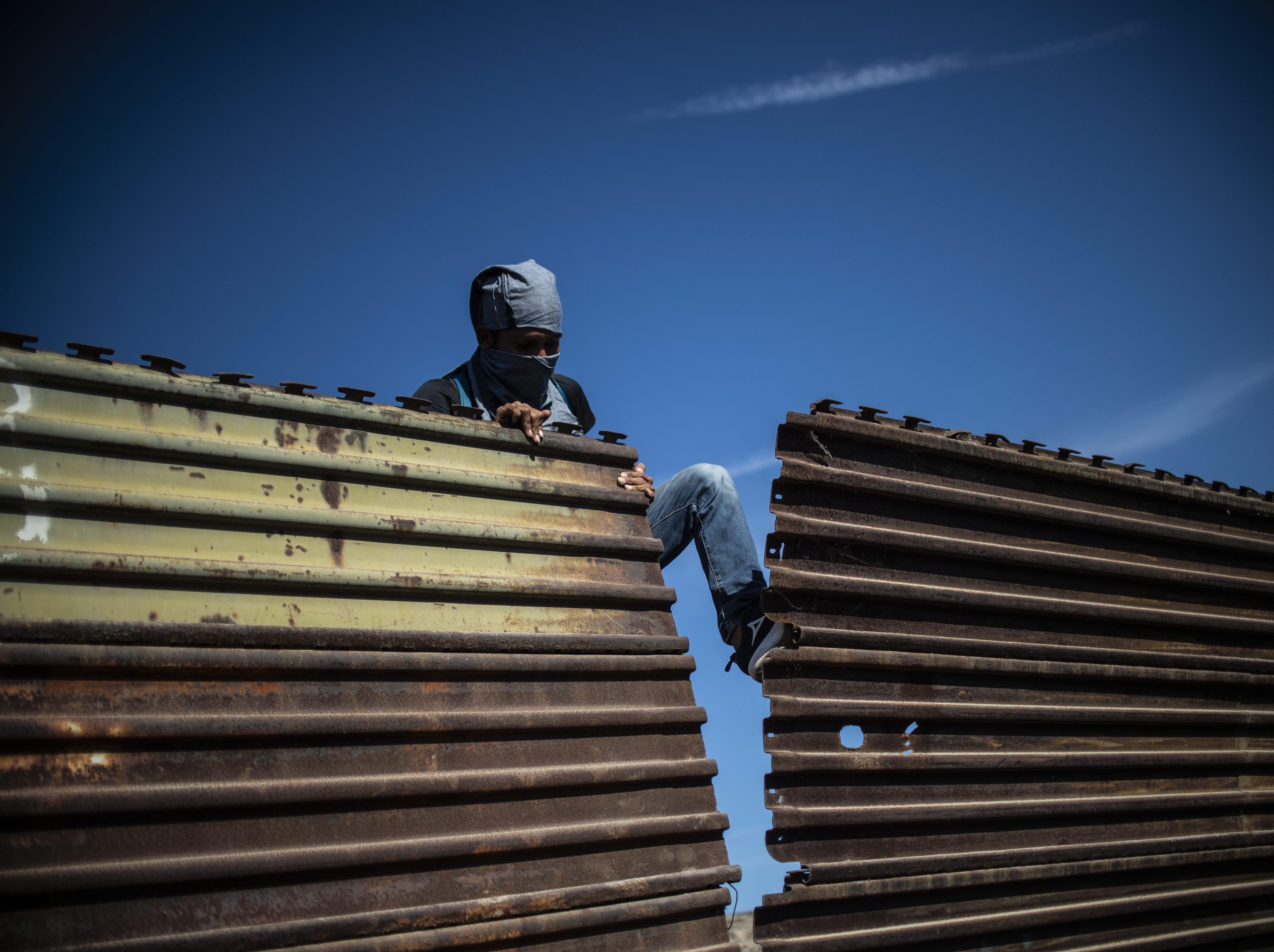 Un migrante centroamericano intenta derribar parte de la cerca fronteriza entre México y los Estados Unidos, cerca del cruce fronterizo de El Chaparral, en Tijuana, estado de Baja California, México, el 25 de noviembre de 2018.