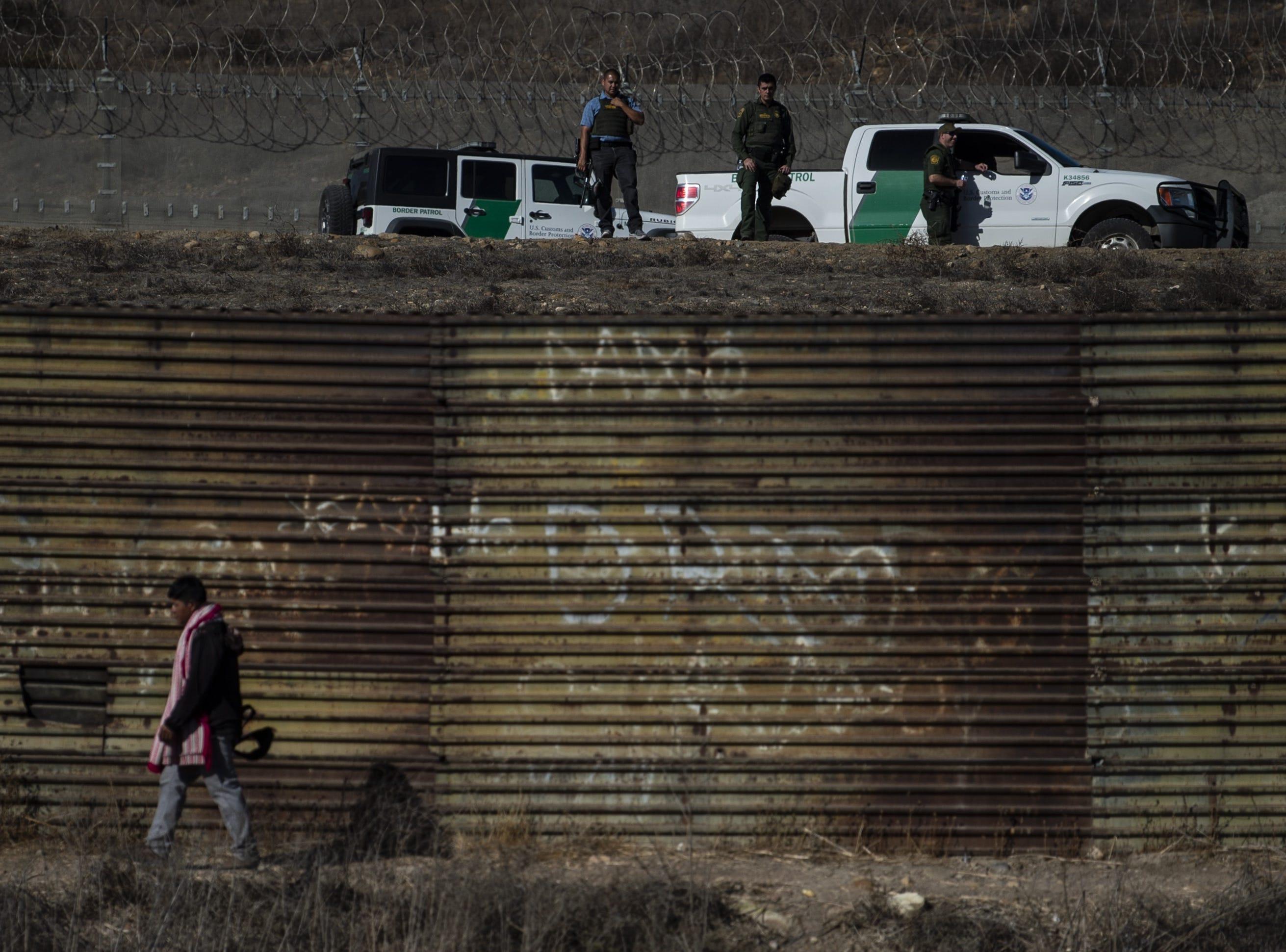Los oficiales de la Patrulla Fronteriza de los EE. UU montan guardia a lo largo de la vía de agua poco profunda del río Tijuana mientras los migrantes centroamericanos, principalmente de Honduras, intentan llegar a suelo estadounidense desde Tijuana, estado de Baja California, México, el 25 de noviembre de 2018.