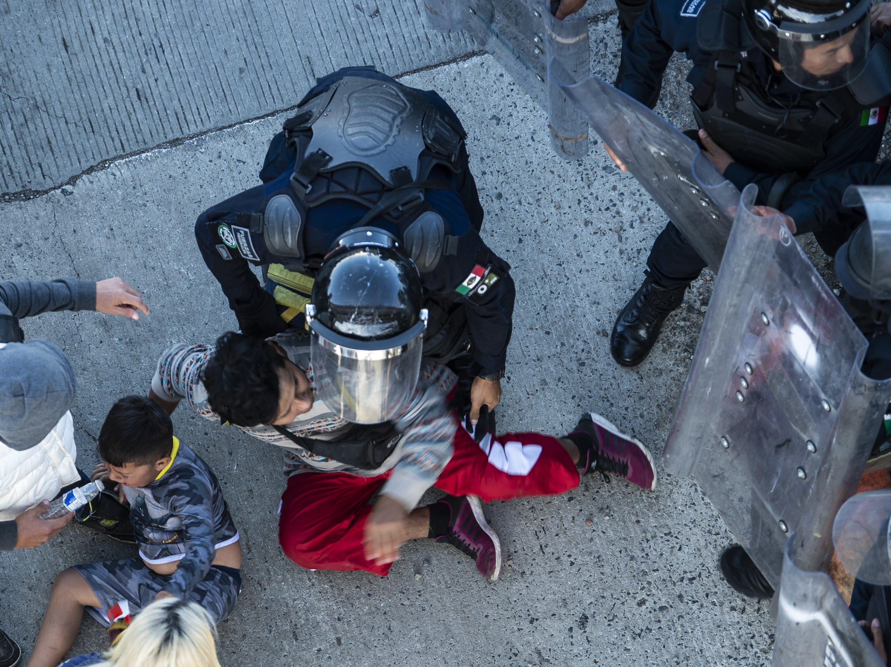 Agentes de la policía mexicana detienen a los migrantes centroamericanos cuando llegan al cruce fronterizo de El Chaparral, en Tijuana, estado de Baja California, México, el 25 de noviembre de 2018 al intentar cruzar la frontera hacia Estados Unidos.