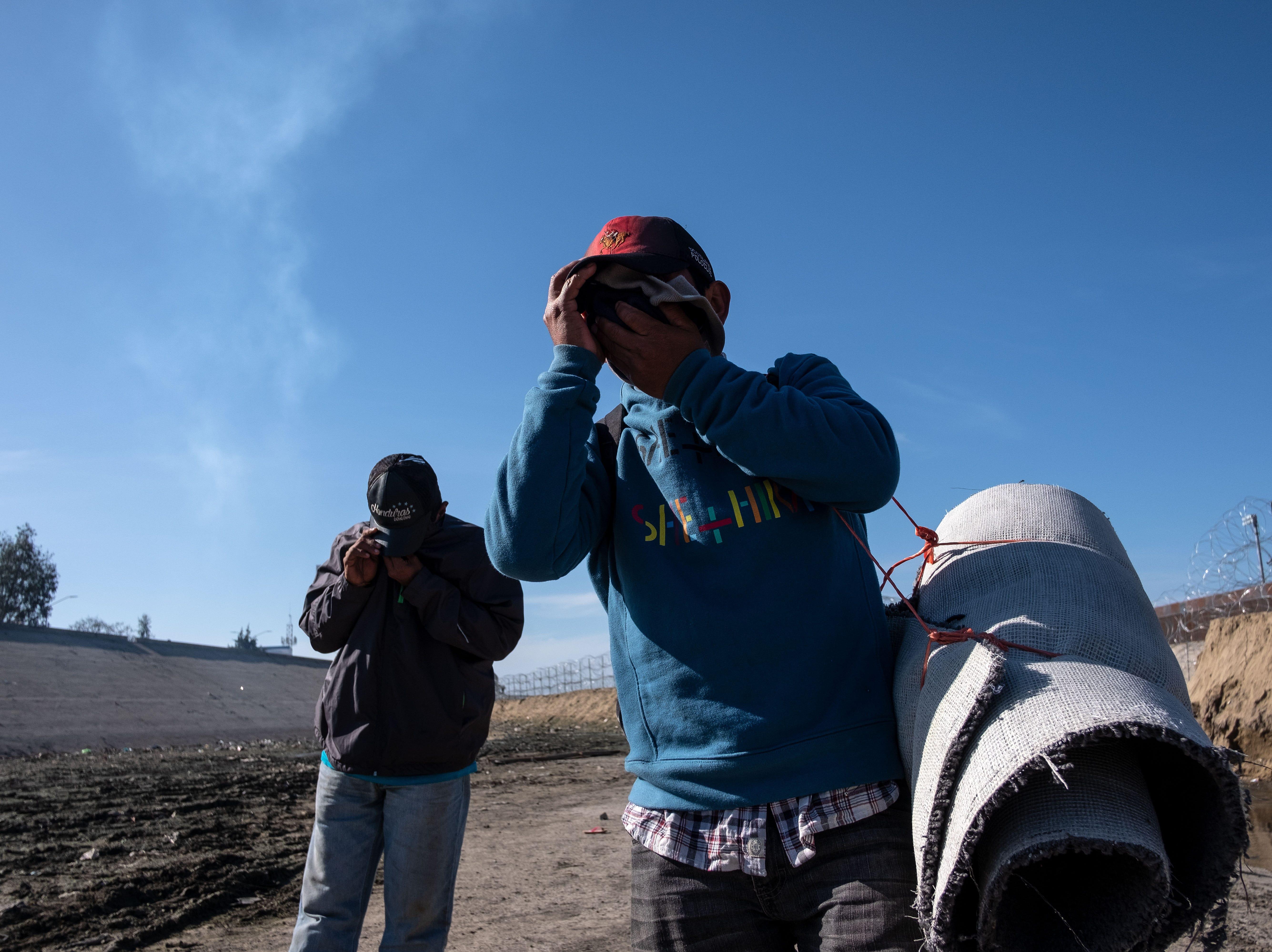 Los migrantes centroamericanos, en su mayoría hondureños, cubren sus rostros al lado del río Tijuana, cerca del cruce fronterizo de El Chaparral en Tijuana, estado de Baja California, México, luego de que la Patrulla Fronteriza de EE. UU. lanzara gases lacrimógenos para dispersarlos después de una supuesta disputa verbal, en noviembre. 25, 2018.