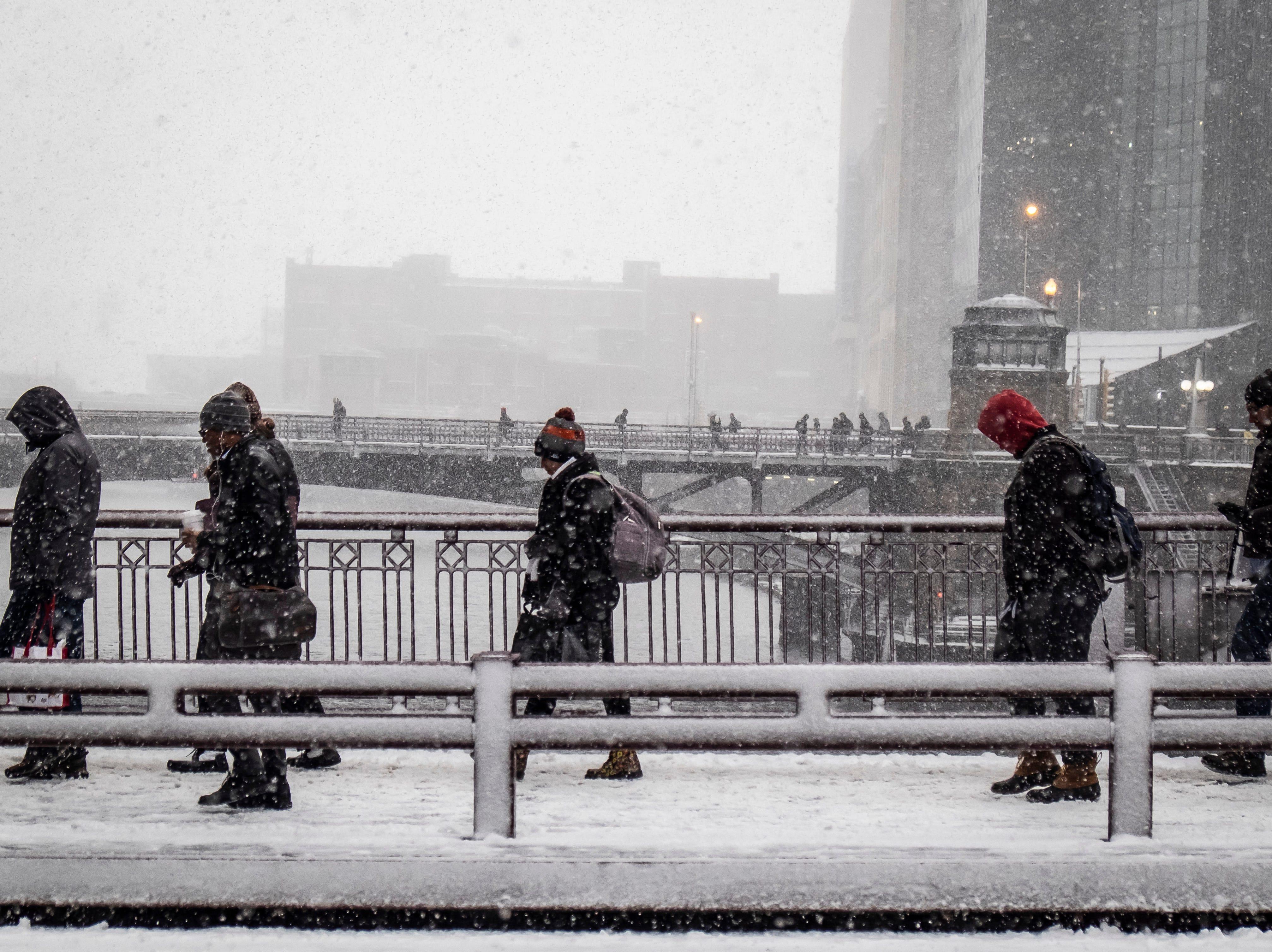 Residentes cruzan el río Chicago en la calle Adams, en Chicago el 26 de noviembre de 2018. Una tempestad invernal trajo condiciones de tormenta de nieve a partes del Medio Oeste el lunes temprano, aterrizando cientos de vuelos y causando un caos en el tráfico mientras los viajeros regresaban al trabajo después del fin de semana de Acción de Gracias.