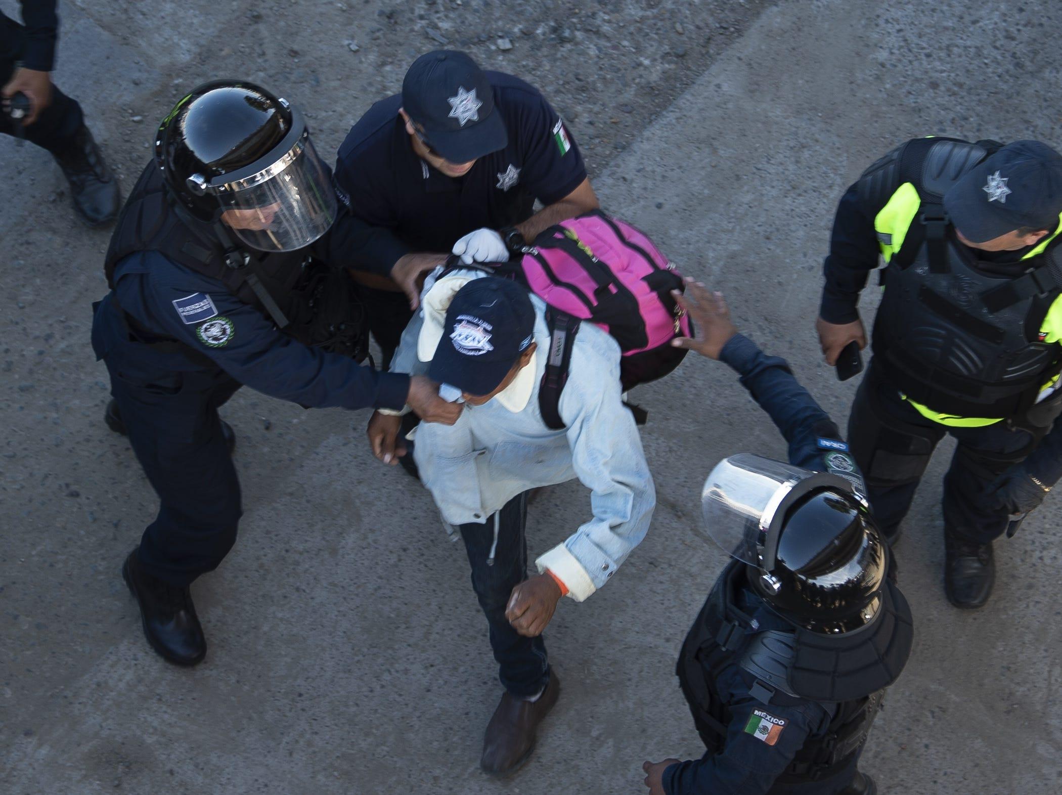 Un migrante centroamericano lucha con las fuerzas policiales mexicanas cuando llega al cruce fronterizo de El Chaparral, en Tijuana, estado de Baja California, México, el 25 de noviembre de 2018.