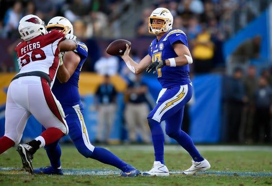 El quarterback Philip Rivers, derecha, de los Chargers de Los Ángeles, lanza en duelo con los Cardinals de Arizona, el domingo 25 de noviembre de 2018, en Carson, California.