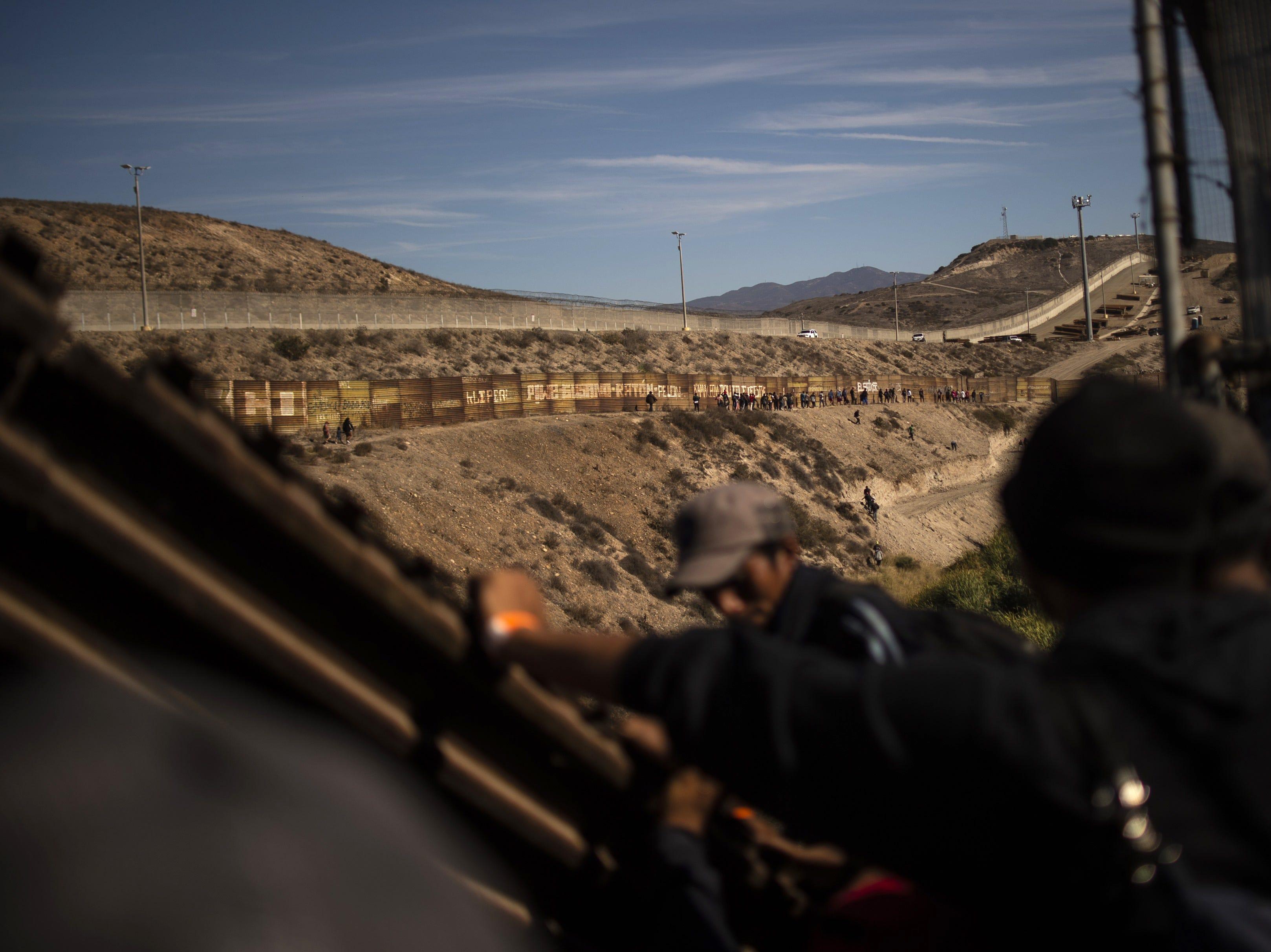 Los migrantes centroamericanos se suben a una barrera de metal en la frontera entre México y EE. UU. Cerca del cruce fronterizo de El Chaparral, en Tijuana, estado de Baja California, México, el 25 de noviembre de 2018.