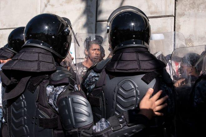 Oficiales de la policía mexicana bloquean el camino a los migrantes centroamericanos, principalmente de Honduras, que desean llegar al cruce fronterizo de El Chaparral cerca de la frontera entre México y Estados Unidos, en Tijuana, estado de Baja California, México, el 25 de noviembre de 2018.
