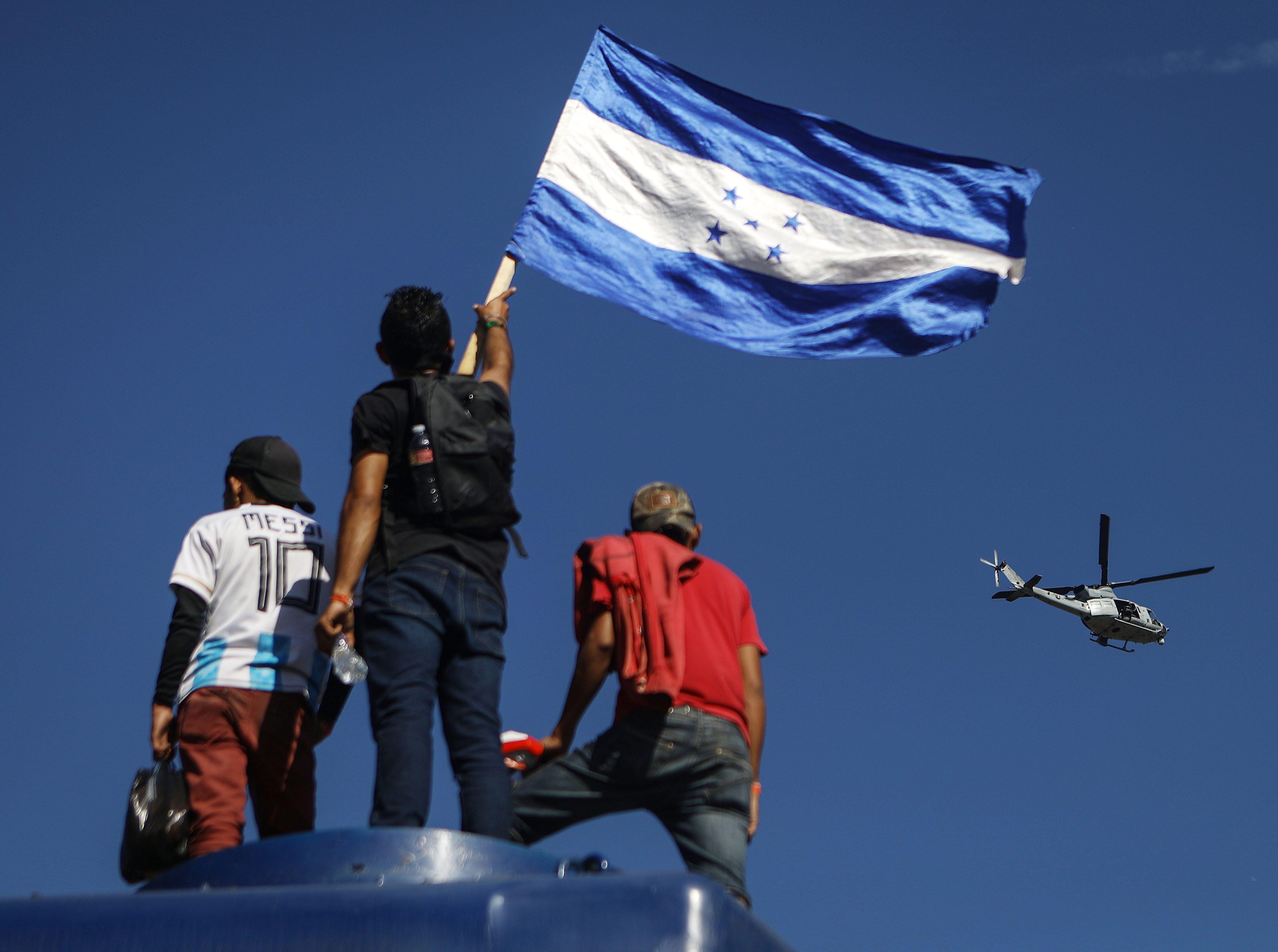 Un helicóptero de la Marina de los Estados Unidos patrulla sobre un migrante ondeando la bandera hondureña mientras se encuentra sobre un vagón de tren cerca de la valla fronteriza de los Estados Unidos y México el 25 de noviembre de 2018 en Tijuana, México.