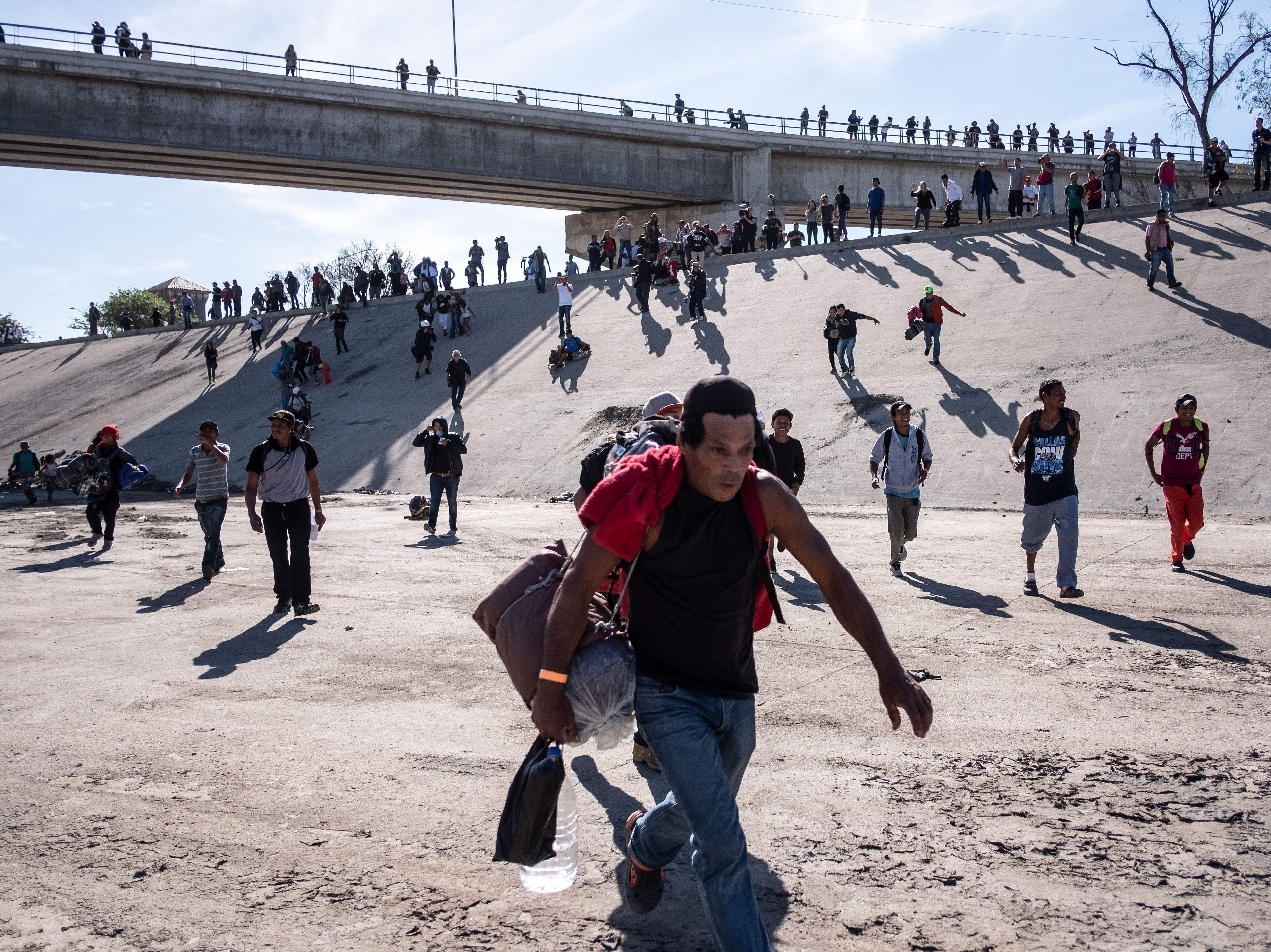 Un grupo de migrantes centroamericanos, principalmente de Honduras, corre a lo largo del lecho seco del río Tijuana en un intento por llegar al puerto de entrada de El Chaparral, en Tijuana, estado de Baja California, México, cerca de la frontera entre Estados Unidos y México el 25 de noviembre de 2018.
