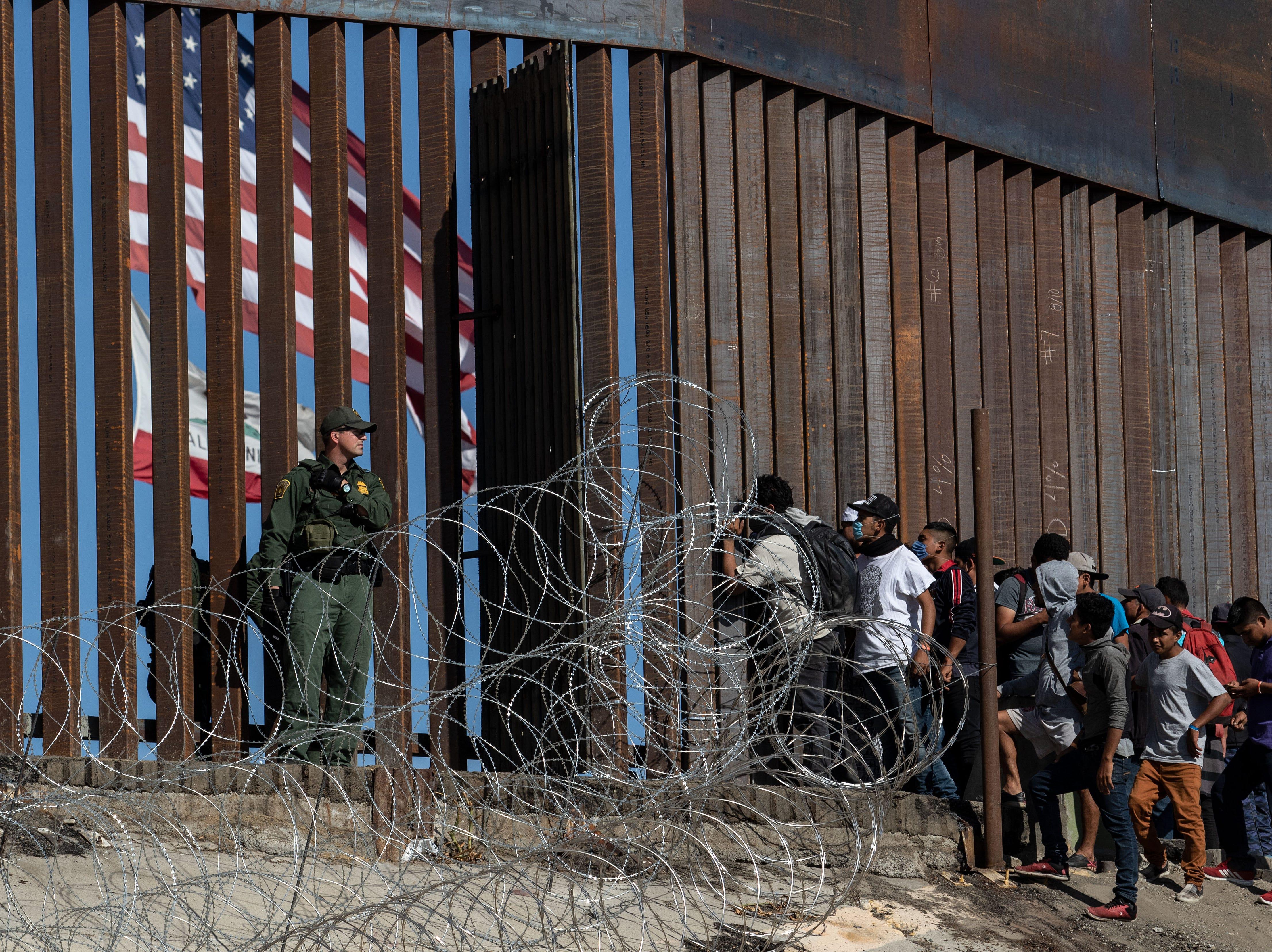 Los migrantes centroamericanos miran a través de una valla fronteriza mientras agentes de la Patrulla Fronteriza de los EE.UU. hacen guardia cerca del cruce fronterizo de El Chaparral en Tijuana, estado de Baja California, México, el 25 de noviembre de 2018.