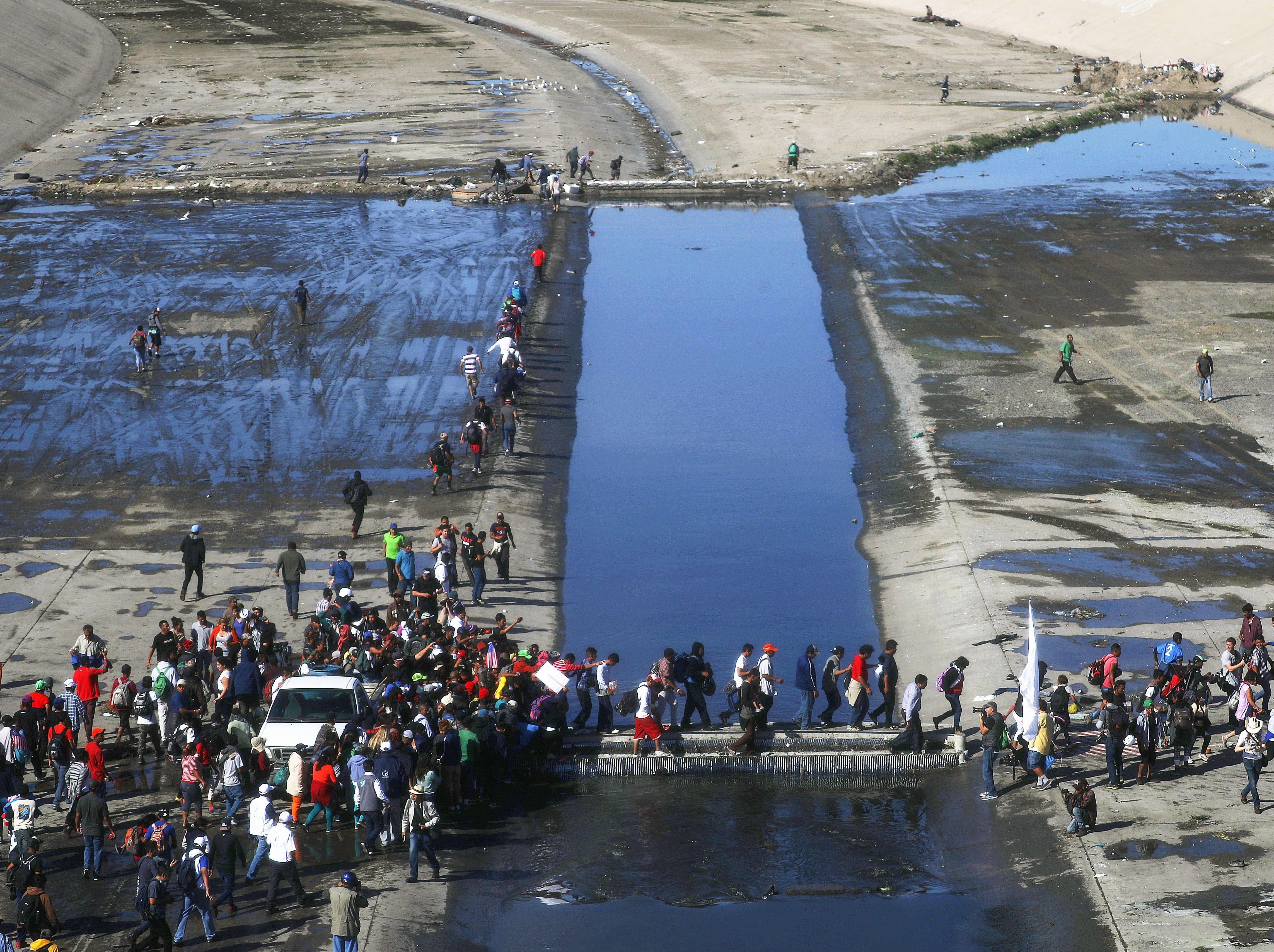 Los migrantes cruzan el río casi seco de Tijuana mientras avanzan alrededor de un bloqueo policial hacia el puerto de entrada de El Chaparral el 25 de noviembre de 2018 en Tijuana, México.