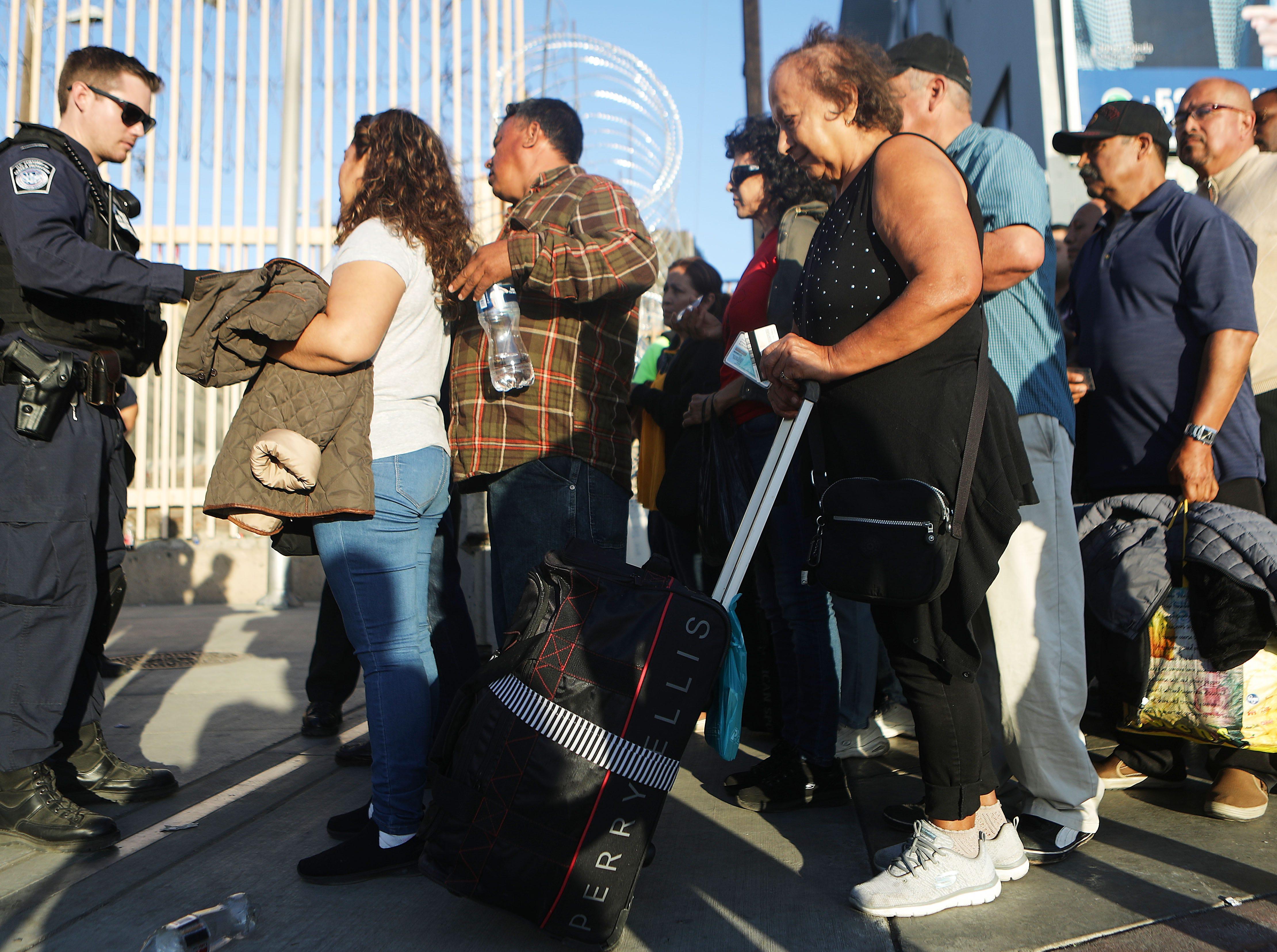Los peatones se preparan para ingresar a los EE.UU en el puerto de entrada de San Ysidro poco después de su reapertura el 25 de noviembre de 2018 en Tijuana, México. La Oficina de Aduanas y Protección Fronteriza de Estados Unidos cerró temporalmente dos puertos de entrada en la frontera con Tijuana en respuesta a un gran grupo de migrantes que se apresuraron a pasar un bloqueo policial hacia la frontera.